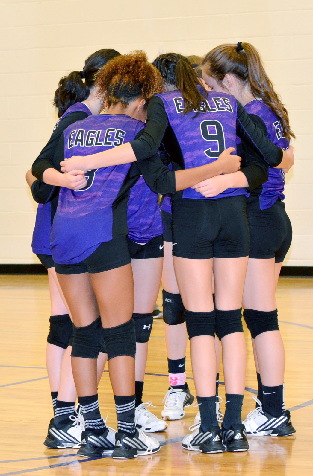 CMS volleyball players huddle before their match.