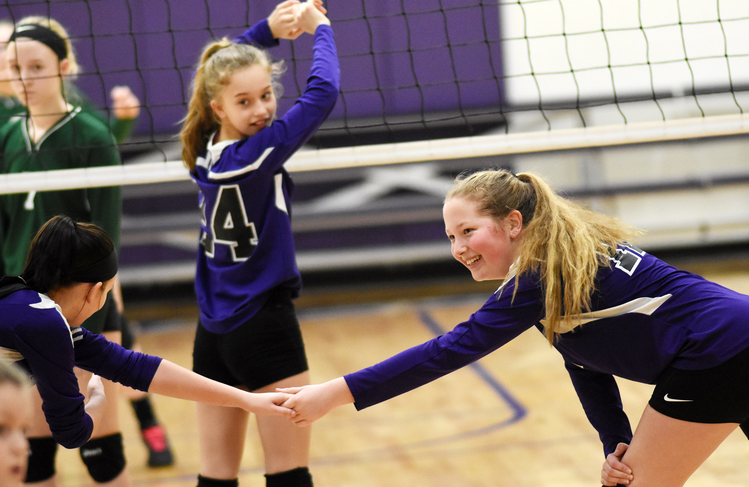 CMS sixth-grader Ava Hughes smiles as her team serves the ball.