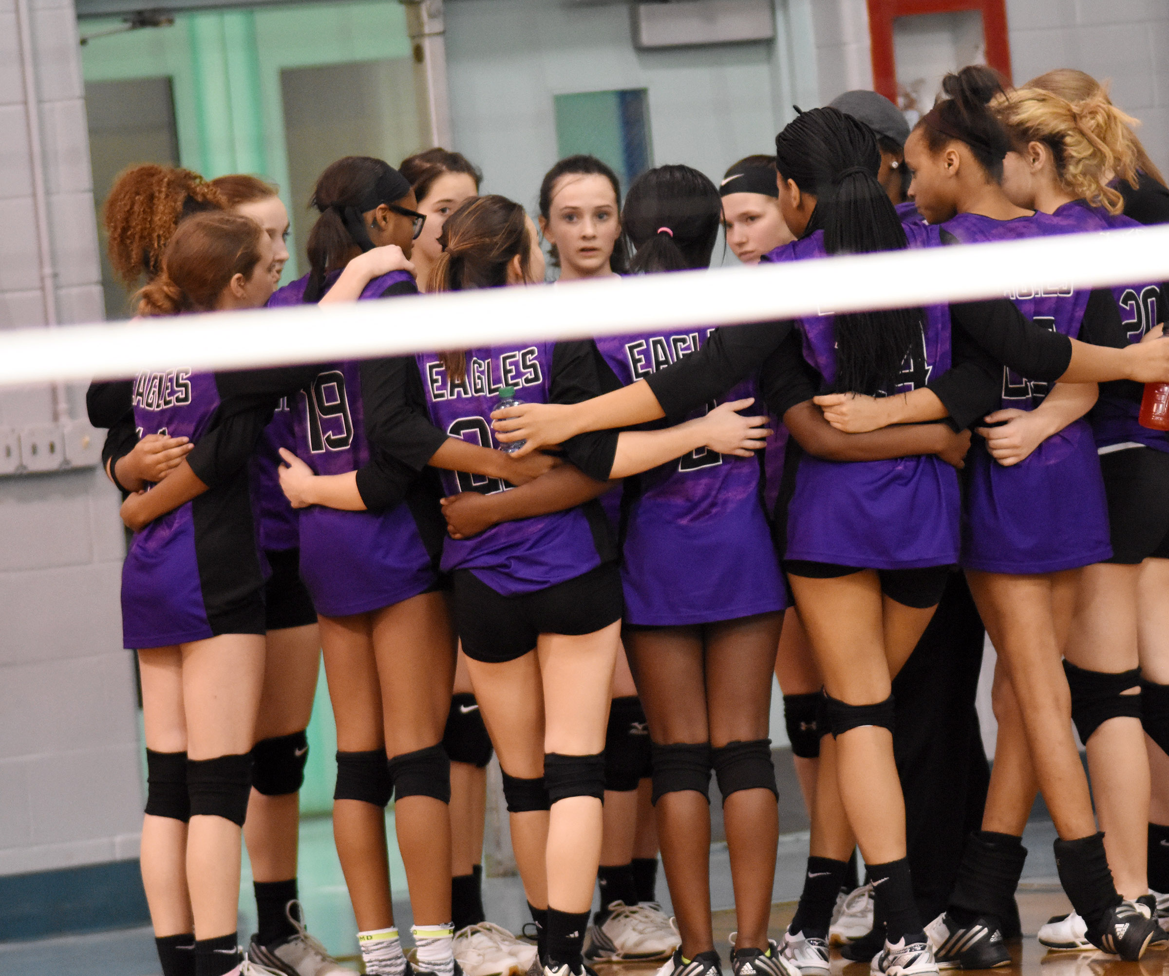 CMS volleyball players huddle.