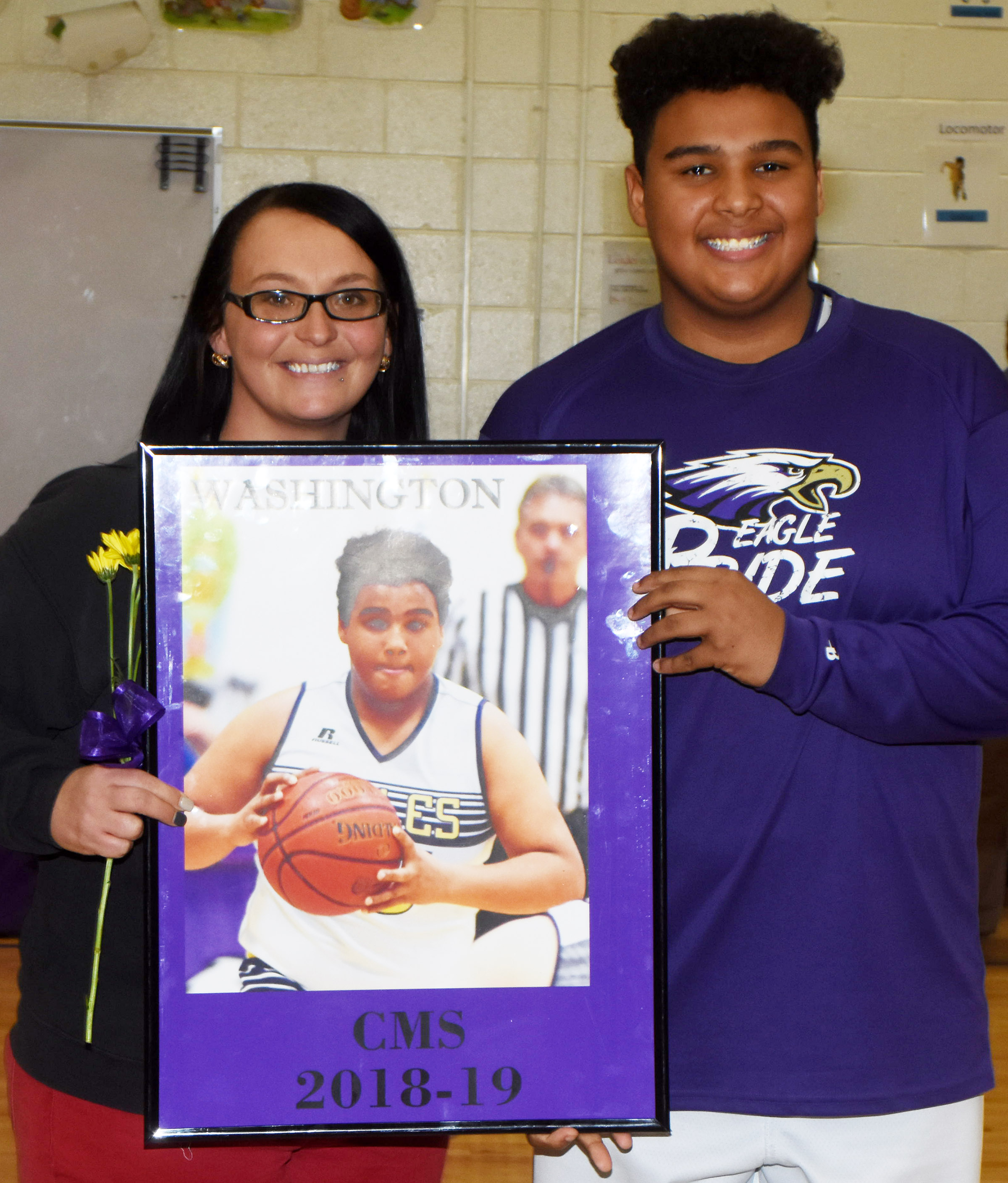 CMS boys' basketball eighth-grader player J.T. Washington is honored.