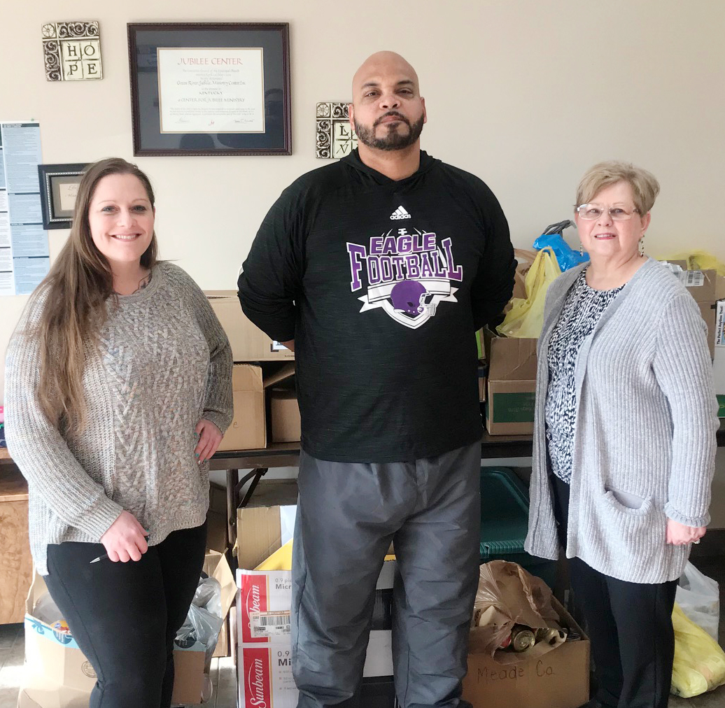 "CMS football head coach Aaron Webb donates canned food items collected at his team's ""Hoops to Help Homeless"" shootout to Taylor County Food Pantry. Pictured with him are Jackie Cherrnay, at left, and Shirley Cheatham of Green River Ministries."