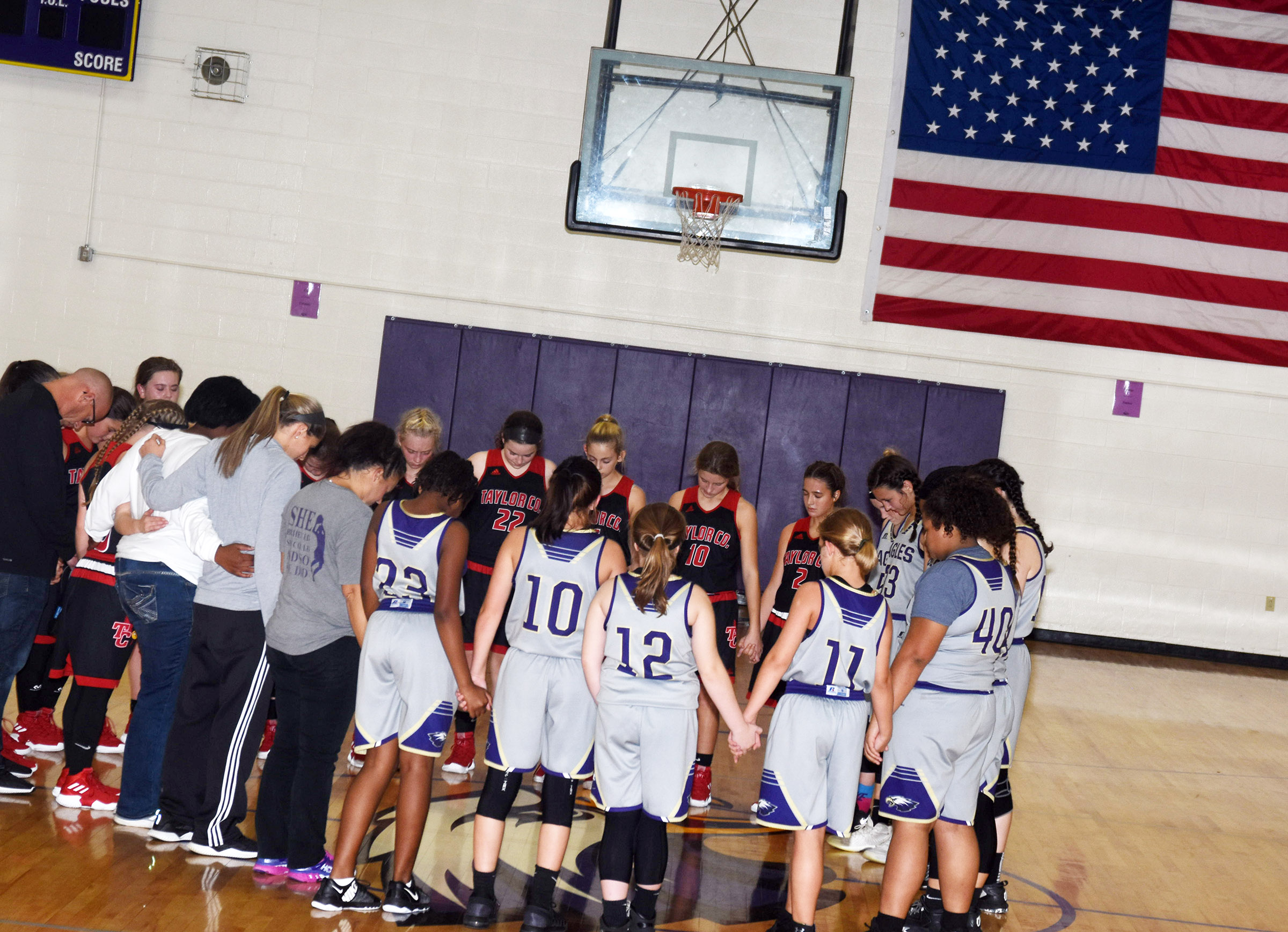 CMS girls' basketball players pray with Taylor County players after the game.