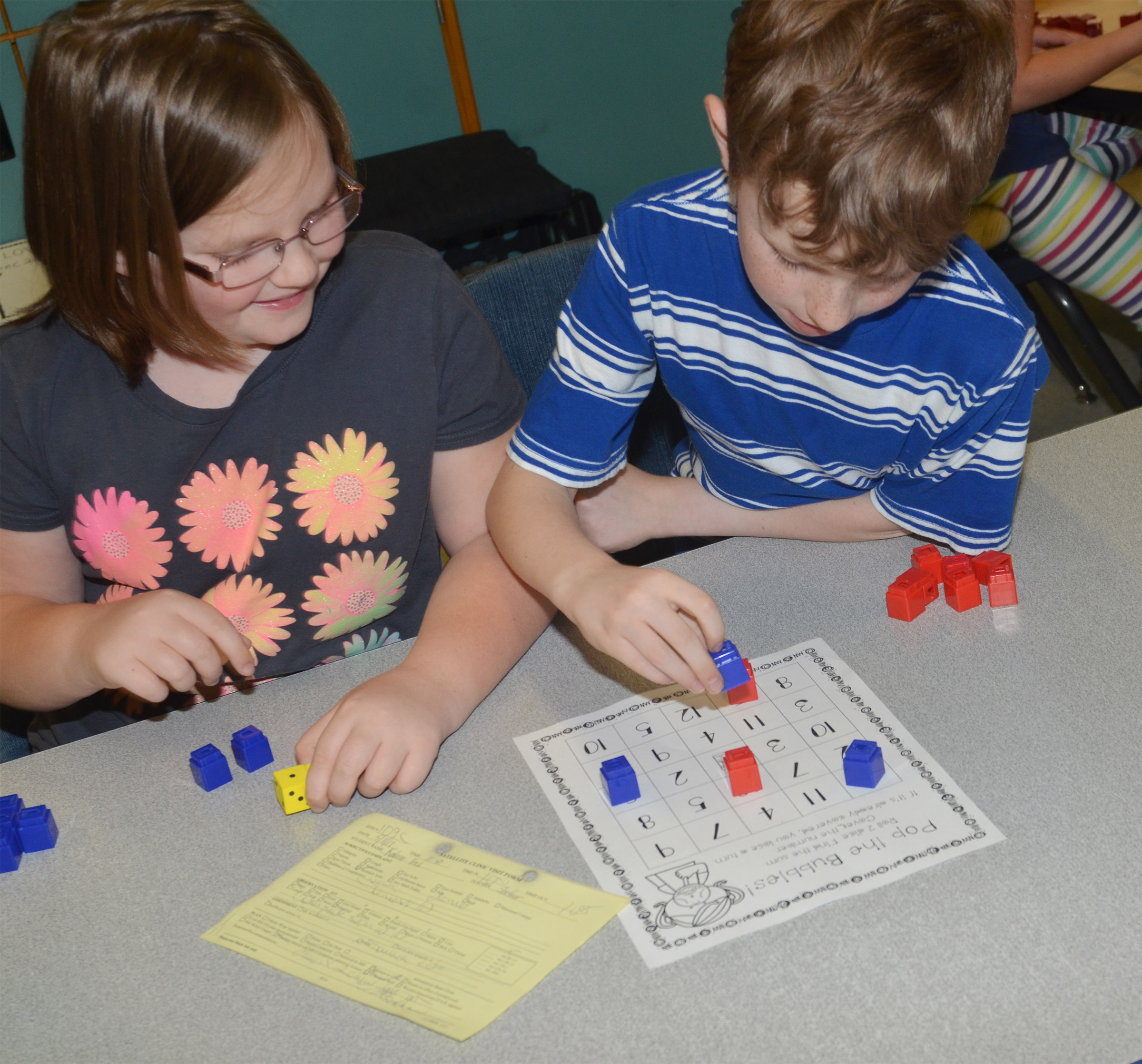 CES first-graders Justice Albrecht, at left, and Jayden Cox play a Pop the Bubble counting game.