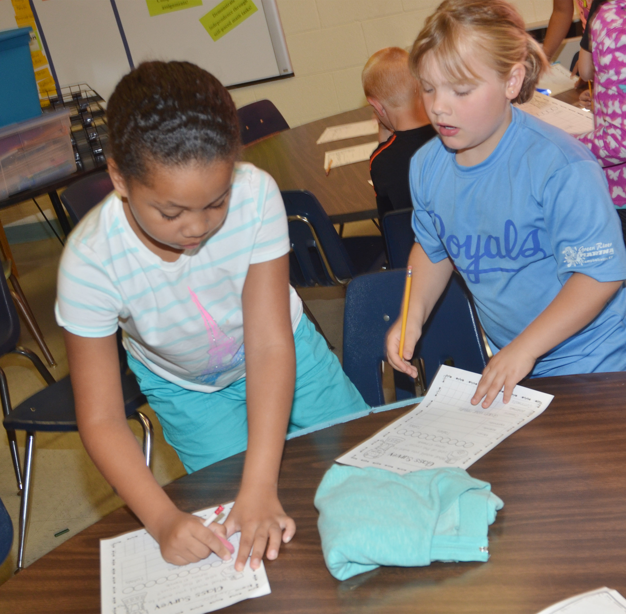 CES first-grader Addysen England, at right, surveys Journey Webb.