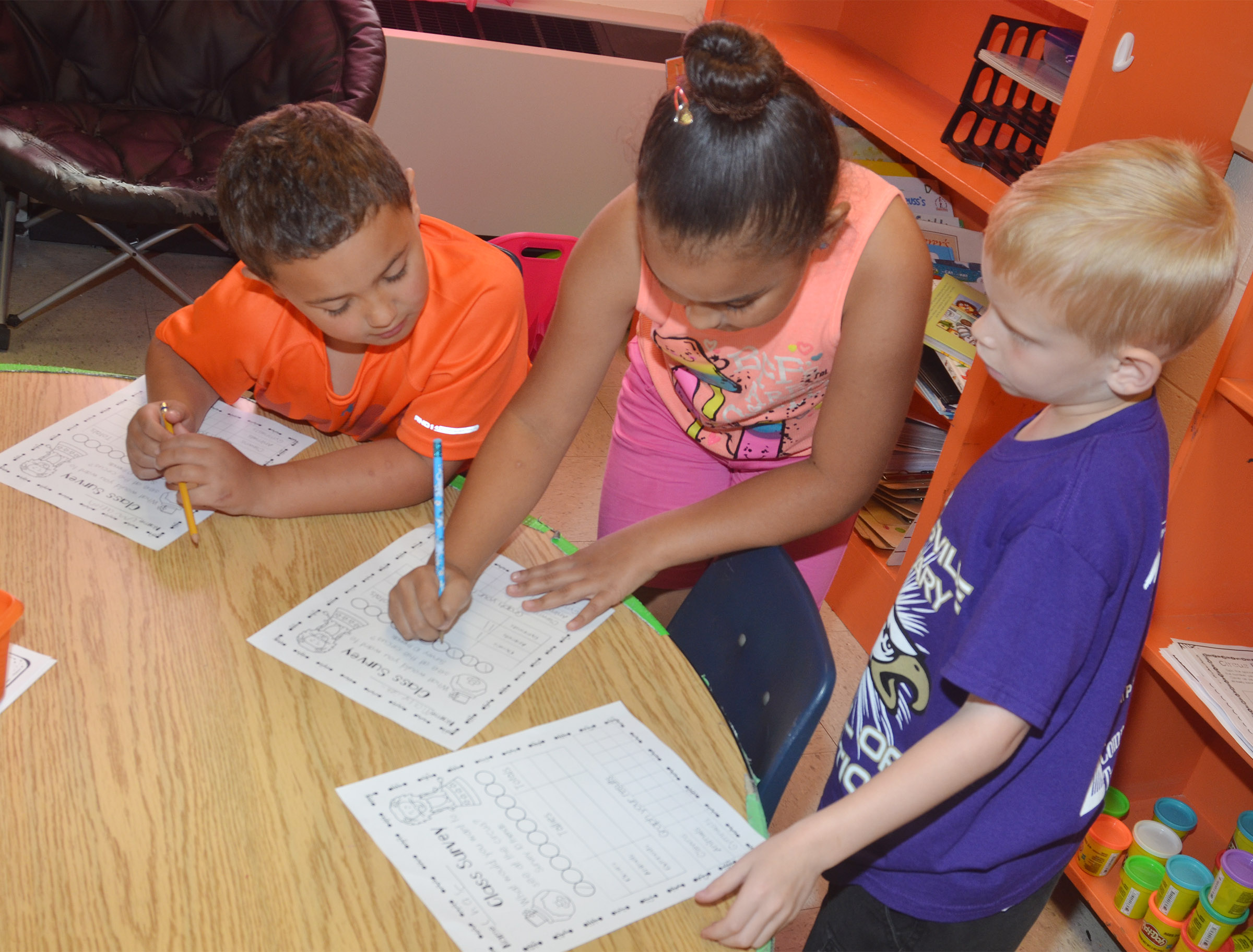 From left, CES first-graders Marion Mann, Maleigha Travis and Chase Gabbert survey each other.