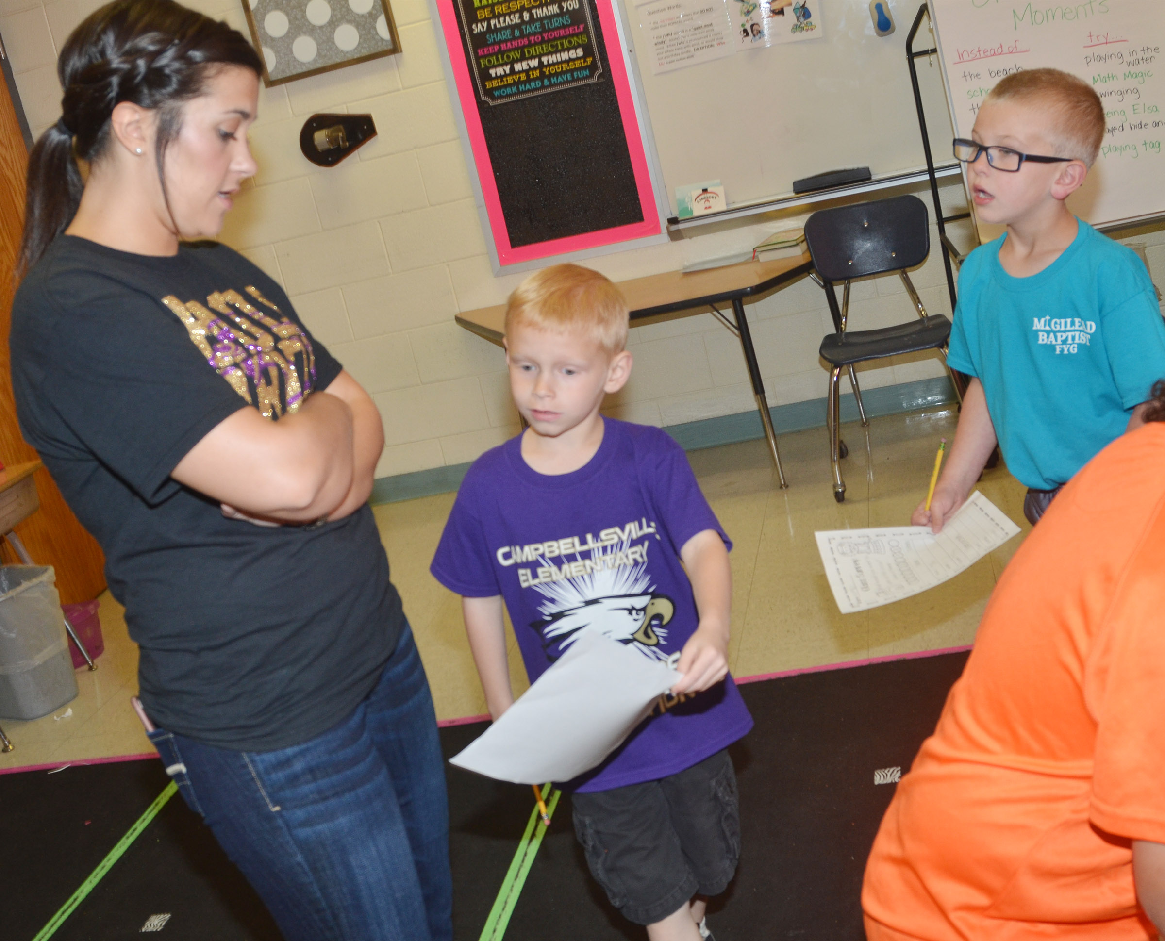 CES first-graders Chase Gabbert, center, and Ethan Bailey survey teacher Hailey Ogle.