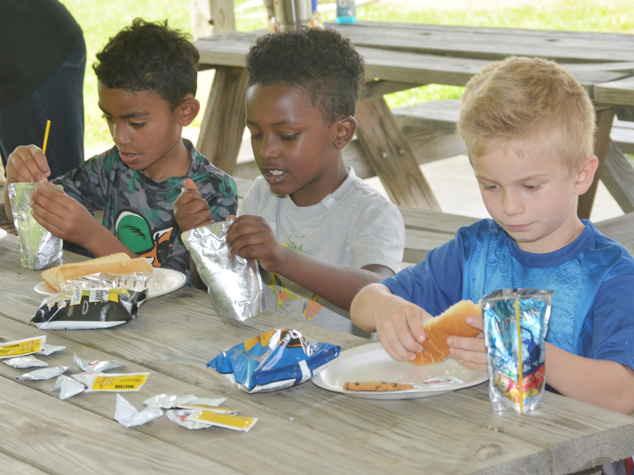 From left, CES first-graders Enoch Smith, Drelynn Hollins and Parker Hamilton enjoy their cookout.
