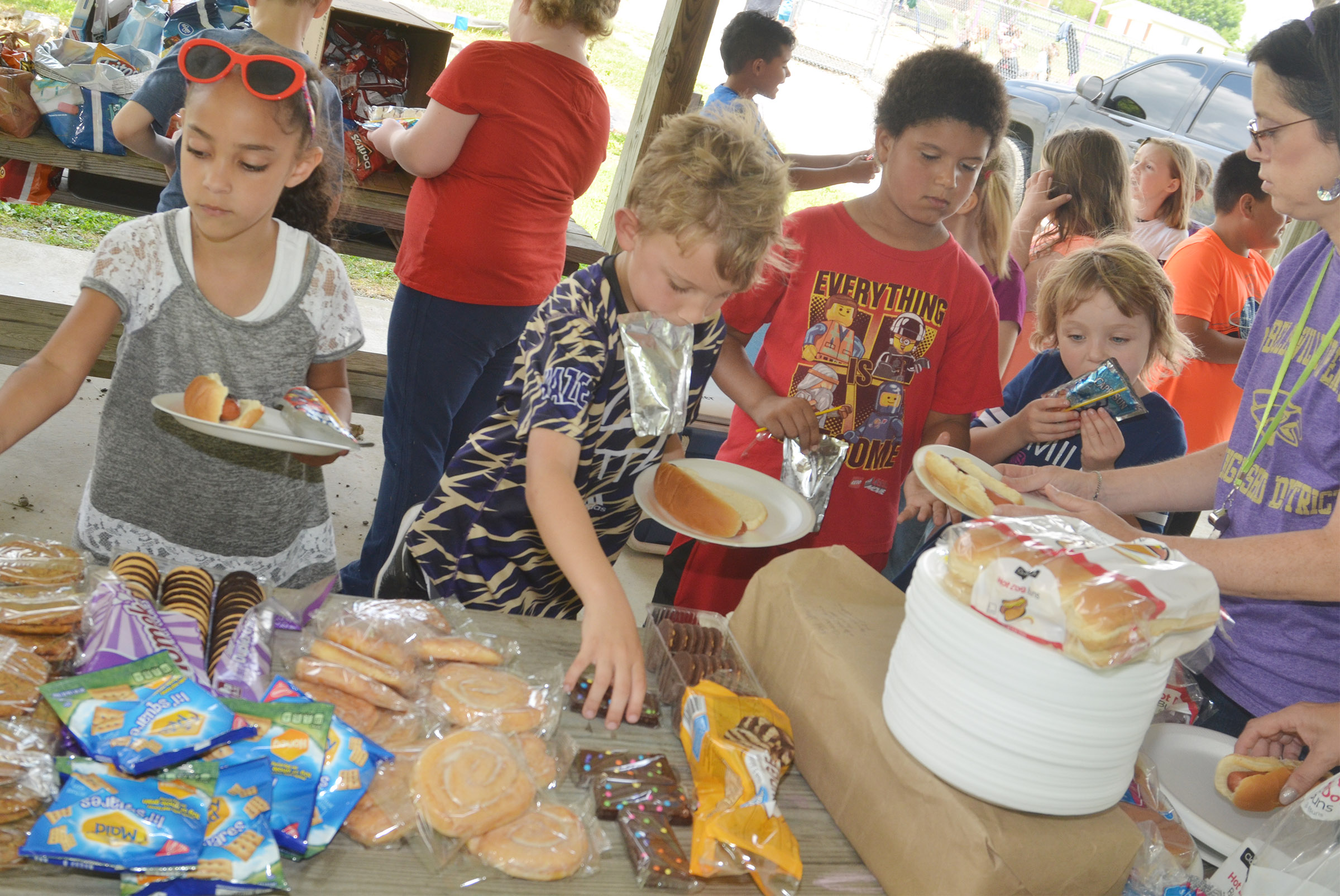 CES first-graders, from left, Essence Hunter, Gabe Prior, Navon Copeland and Mylee Bell get food at their cookout.