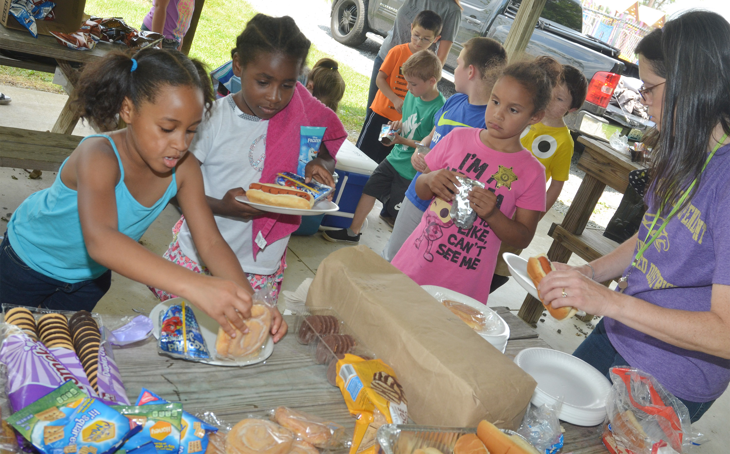 CES first-graders Kadance Ford, at left, and Destini Gholston get their food at the cookout.
