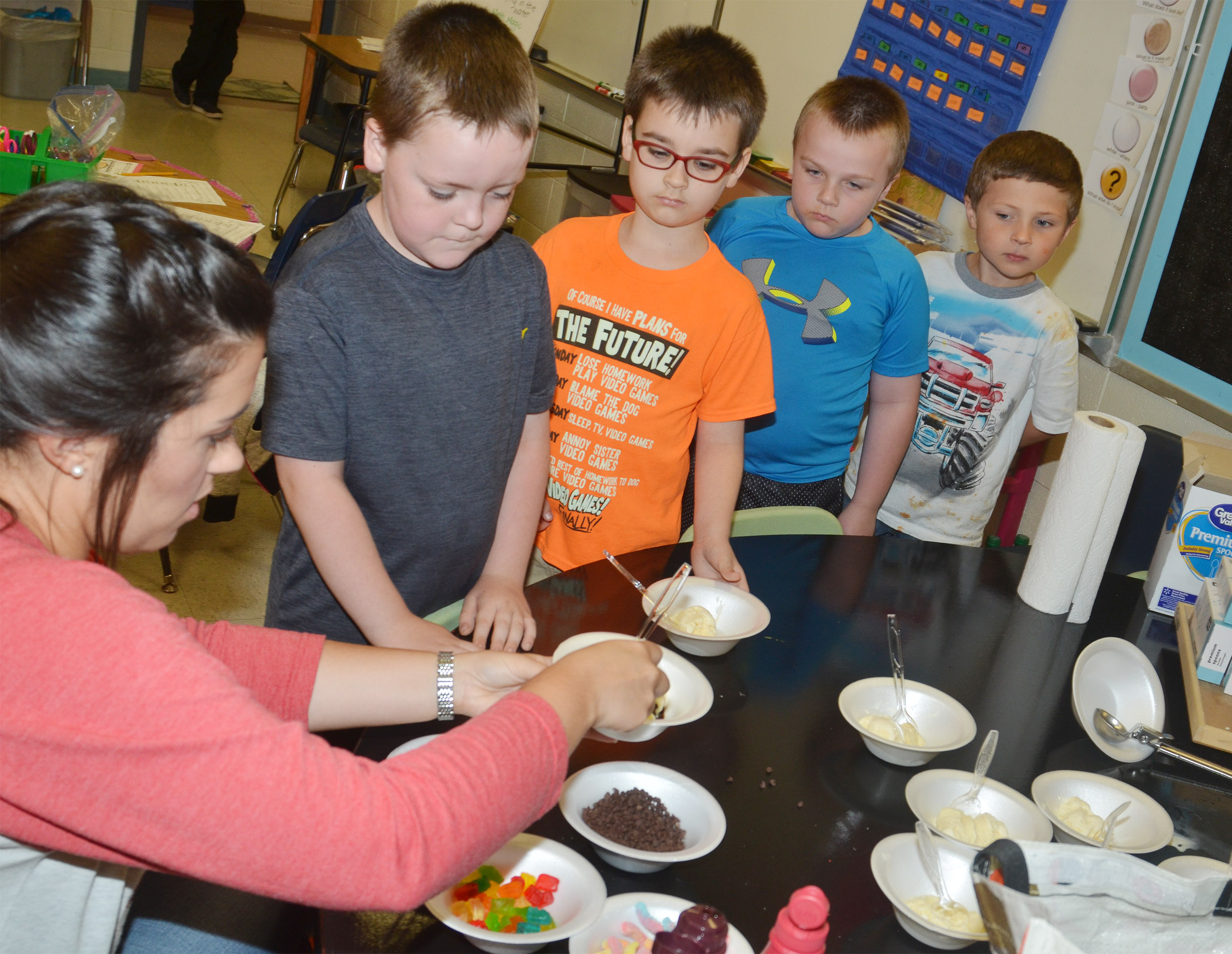 CES first-grade teacher Hailey Ogle serves Eric Epperson some sprinkles on his ice cream sundae.