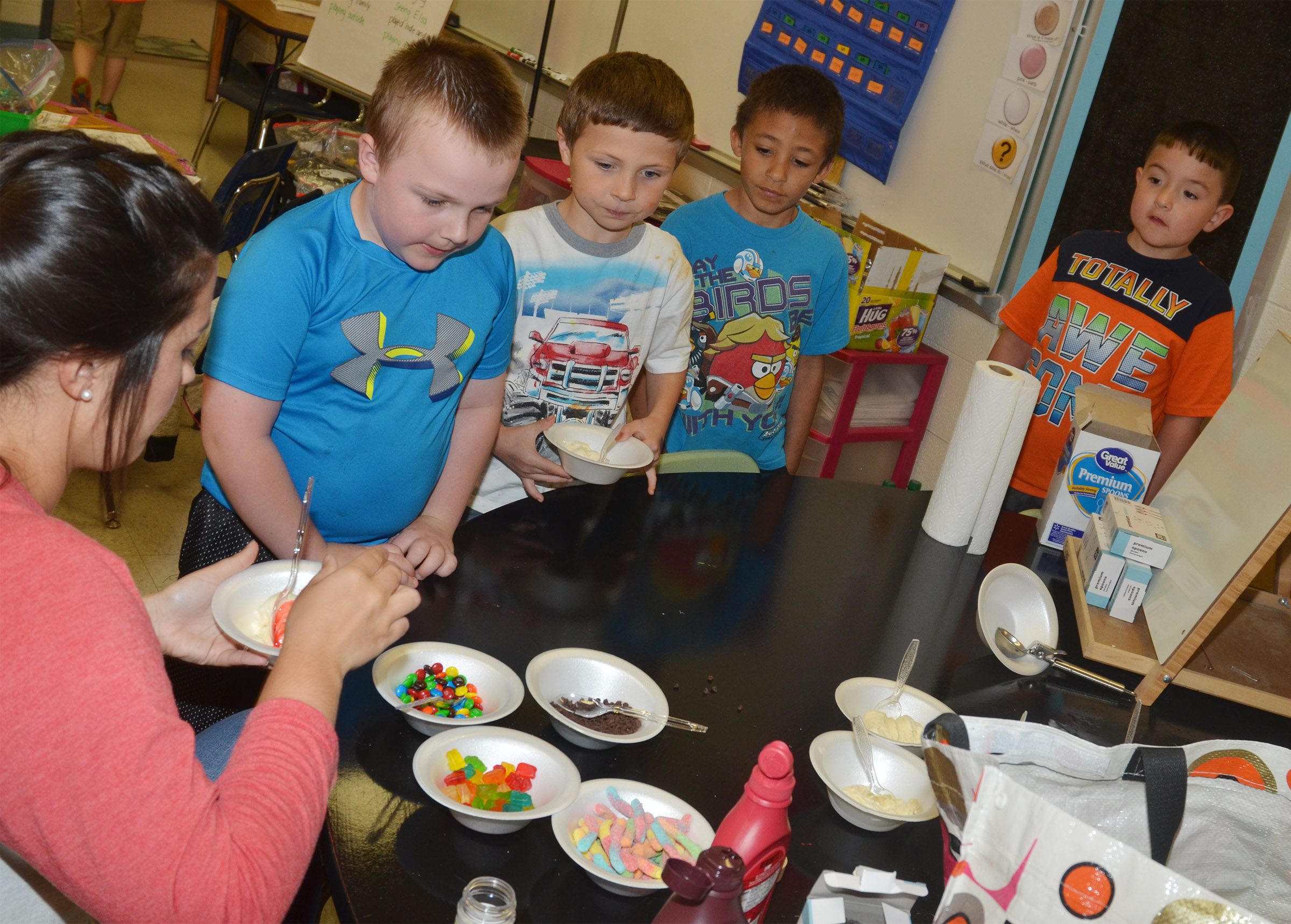 CES first-grade teacher Hailey Ogle serves Hunter Clark an ice cream sundae with strawberry syrup.