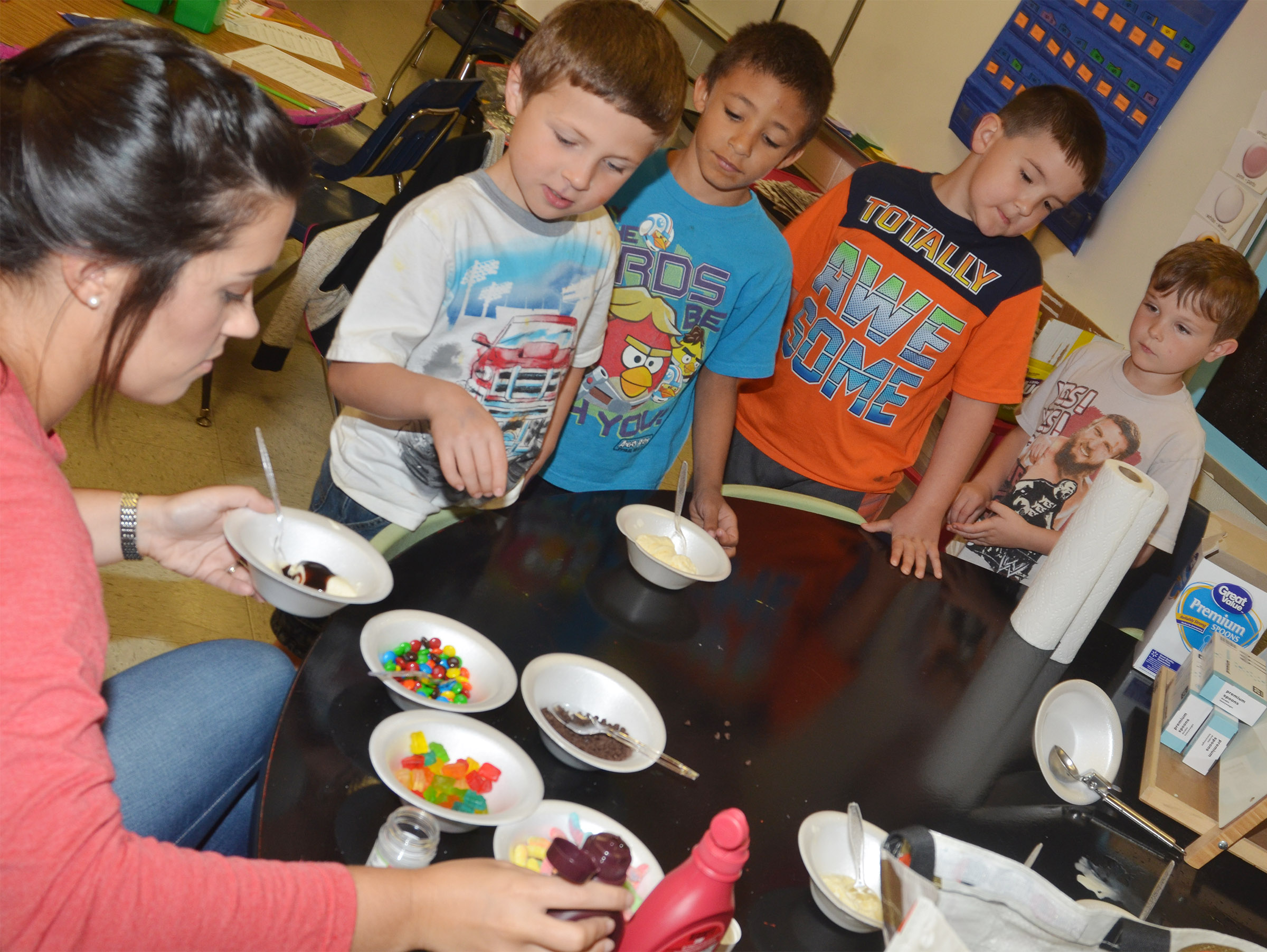CES first-grade teacher Hailey Ogle serves Bryson Gabehart an ice cream sundae with chocolate syrup.