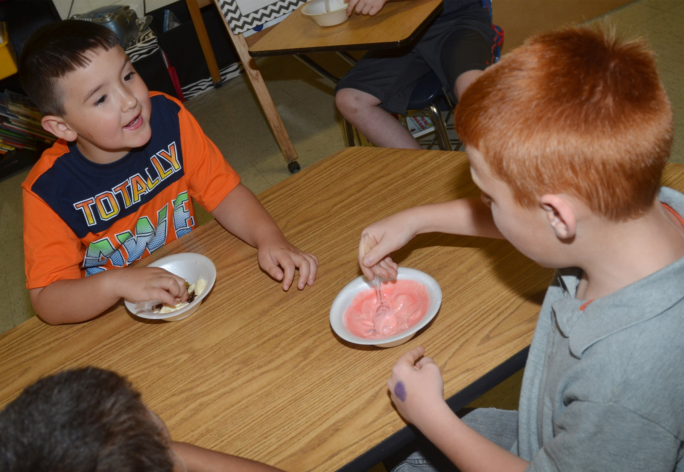 CES first-grader Braxton Giles-Osinger talks to classmate Carter Wethington as they enjoy their ice cream sundaes.