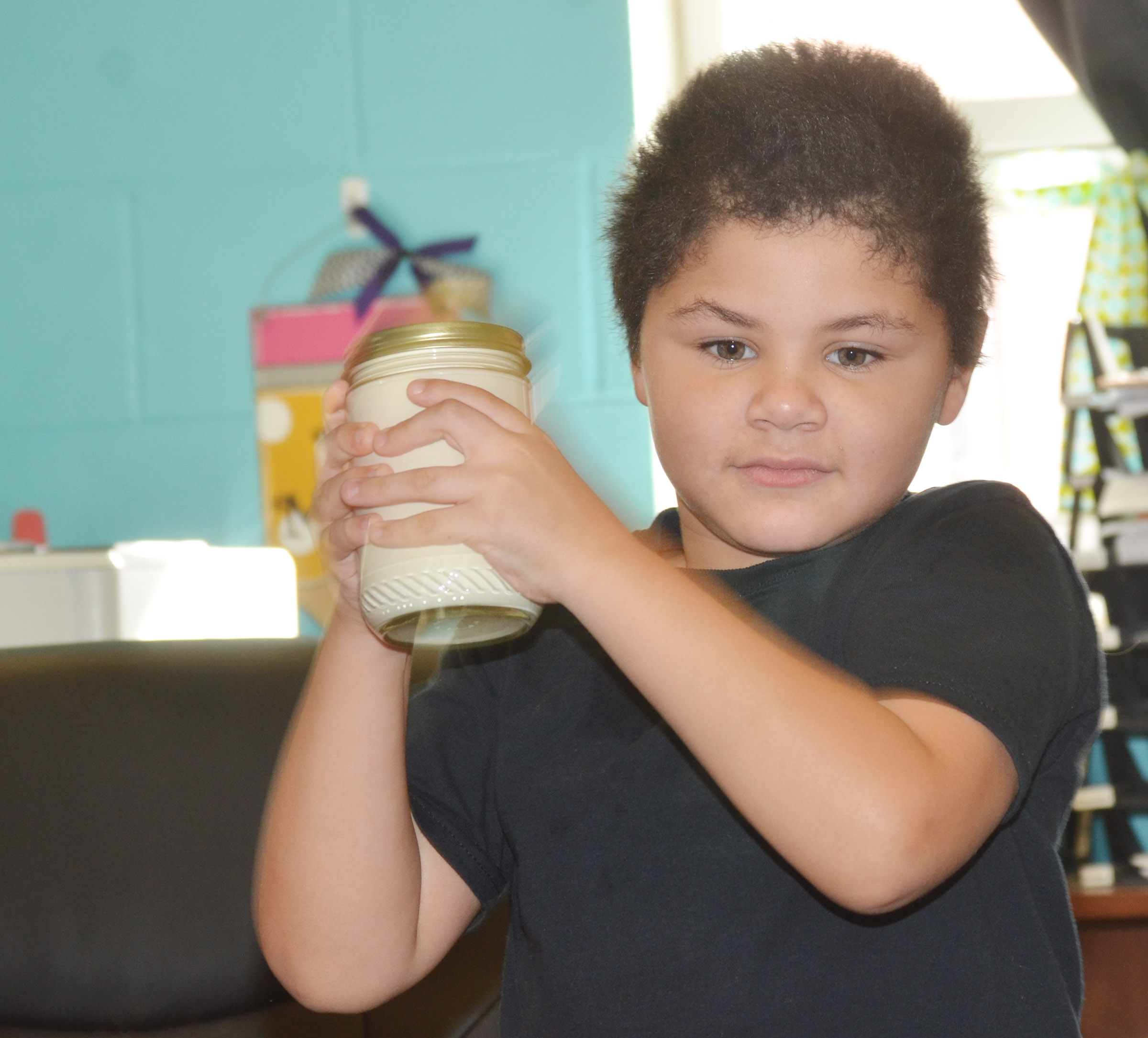 CES first-grader NyJah Vaught shakes the class's jar of butter.
