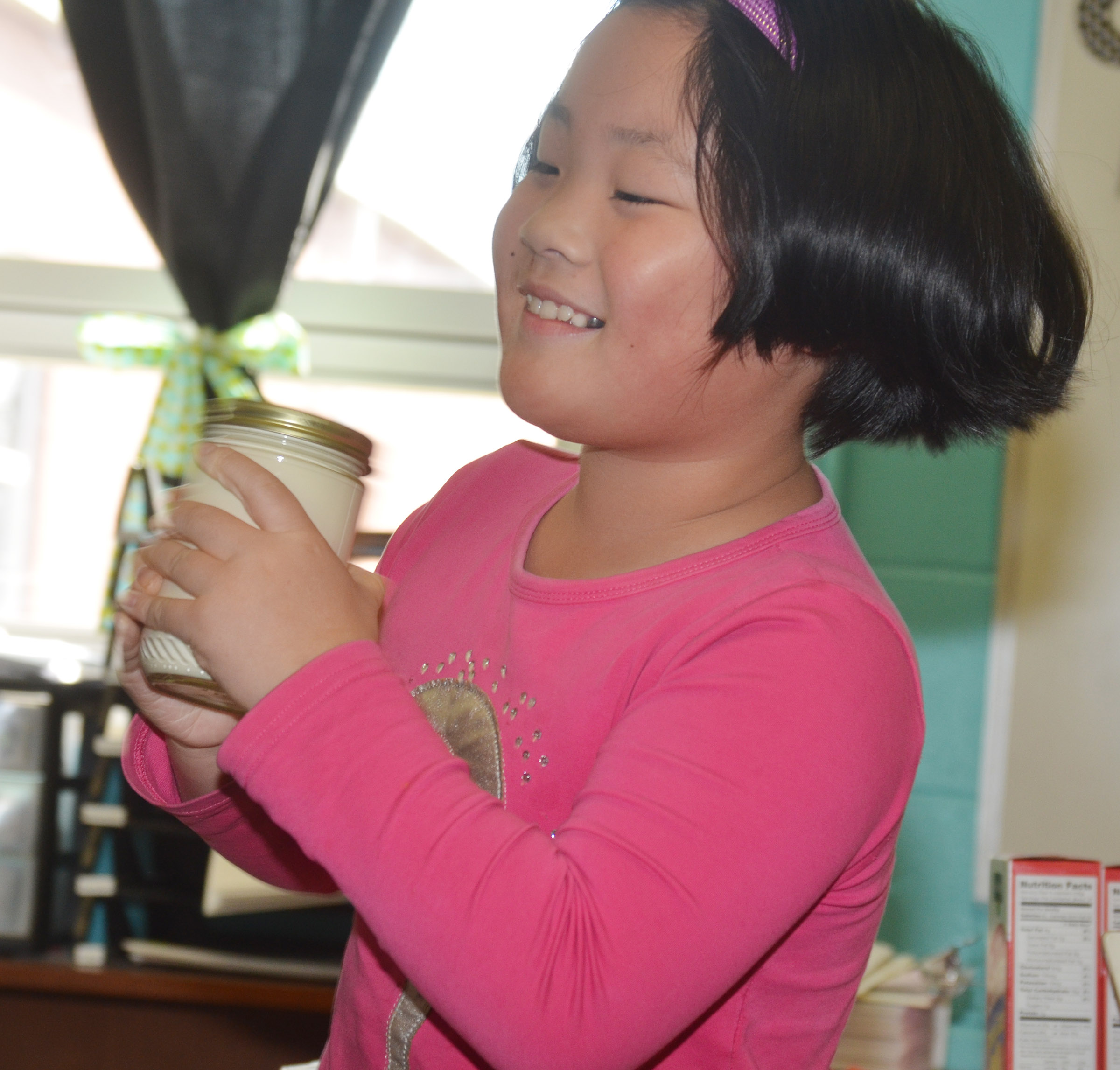 CES first-grader Vicky Li shakes the class's jar of butter.