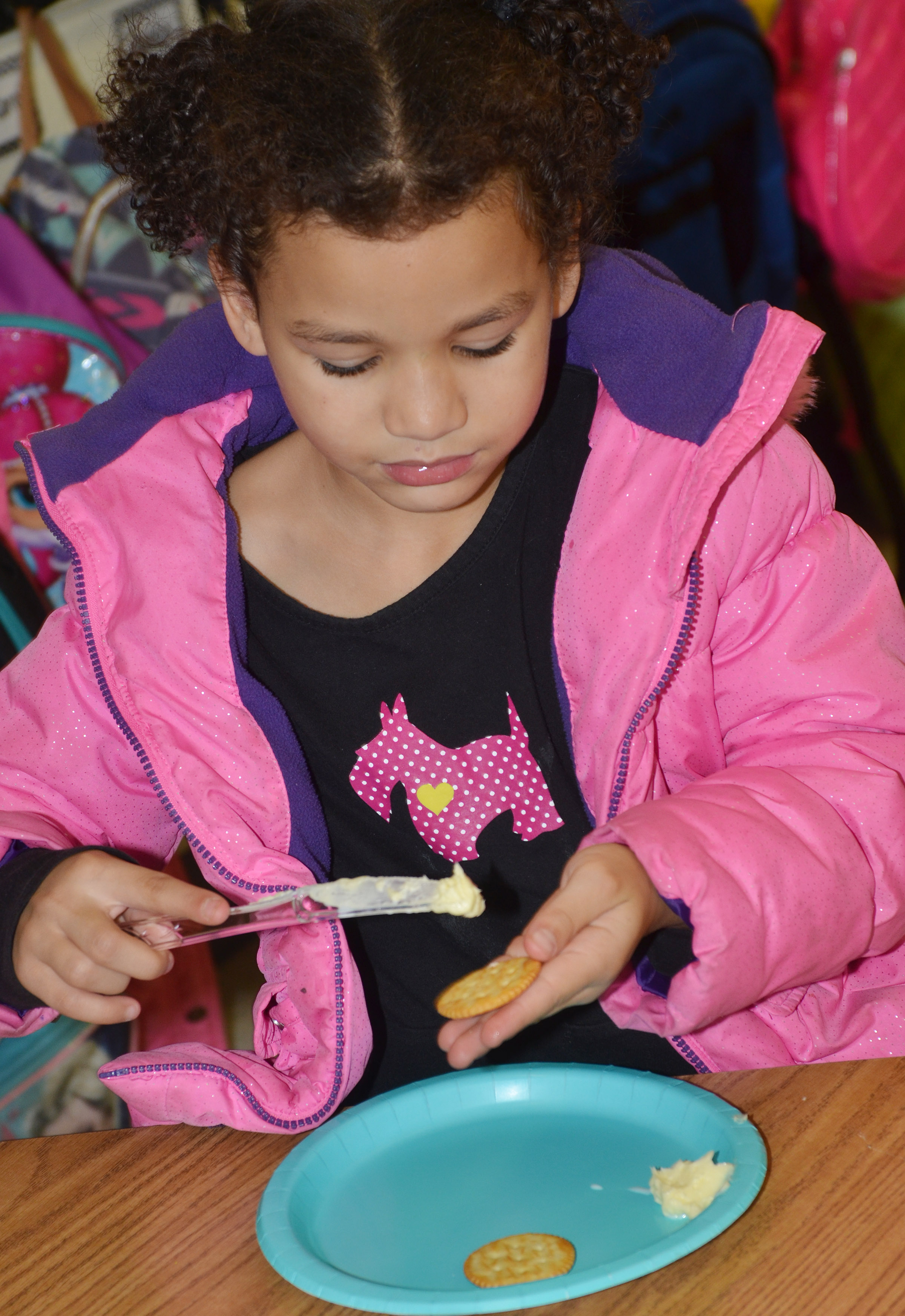 CES first-grader Aleeya Spaulding tastes the butter she and her classmates made.