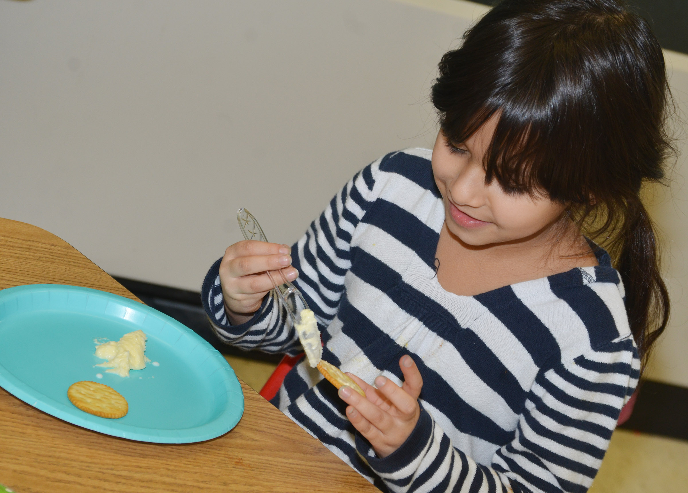 CES first-grader Carol Moura tastes the butter she and her classmates made.