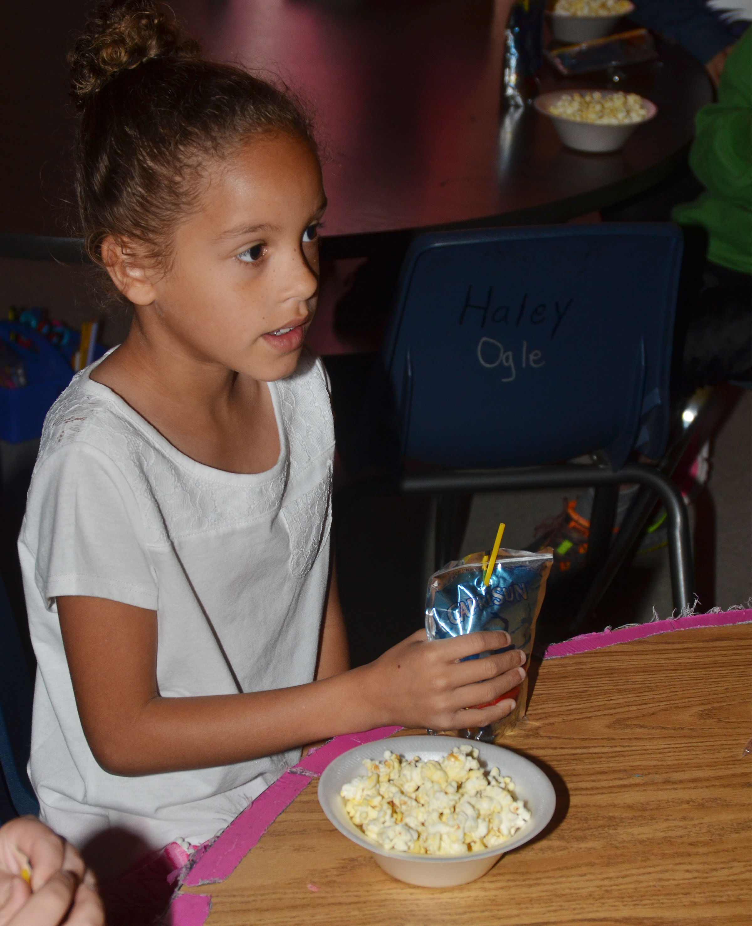 CES first-grader Keiava Thompson enjoys her popcorn snack.