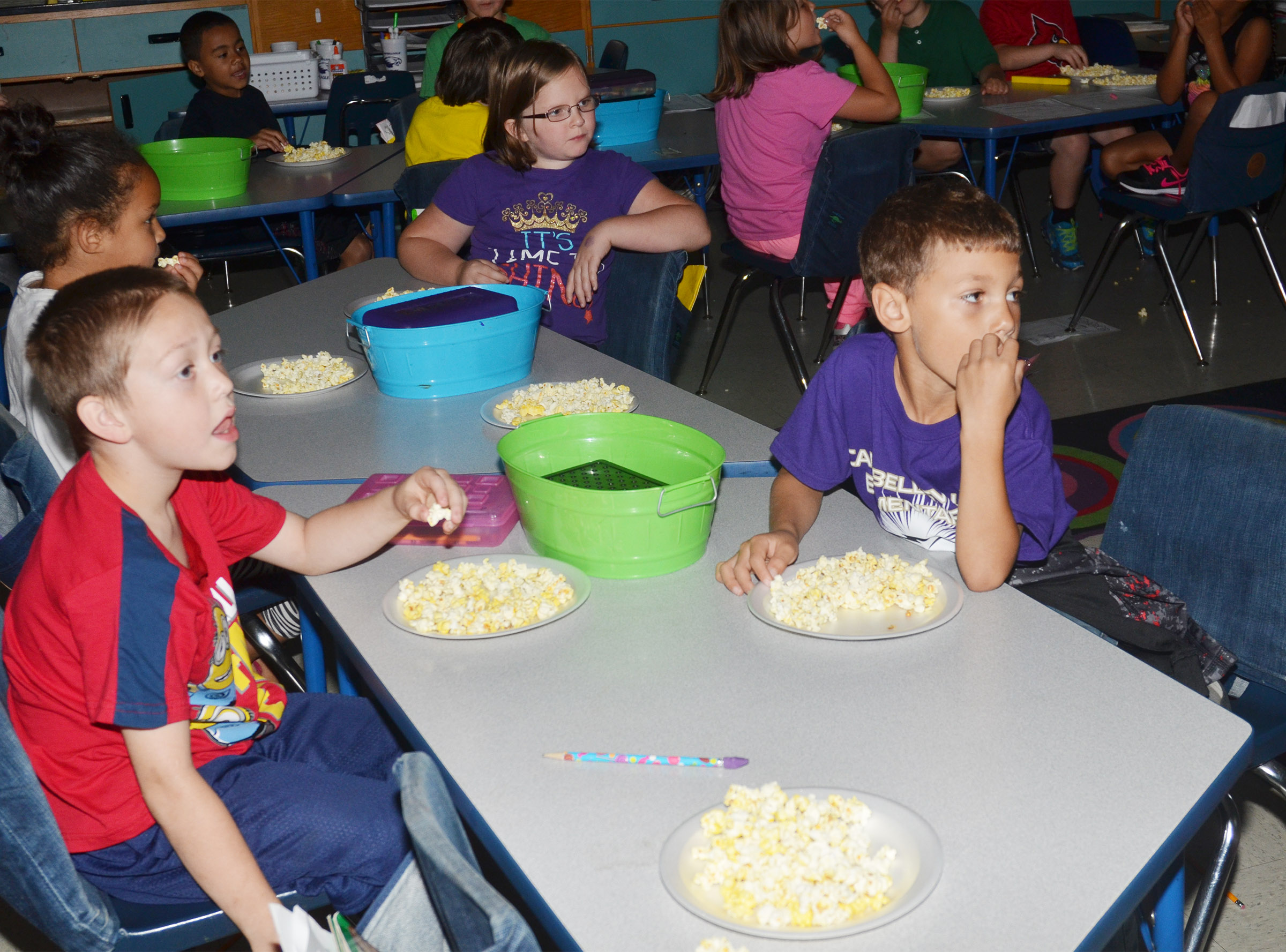 CES first-graders, from left, Jacob Golden, Justice Albrecht and Shylan Dunn enjoy their popcorn snack.