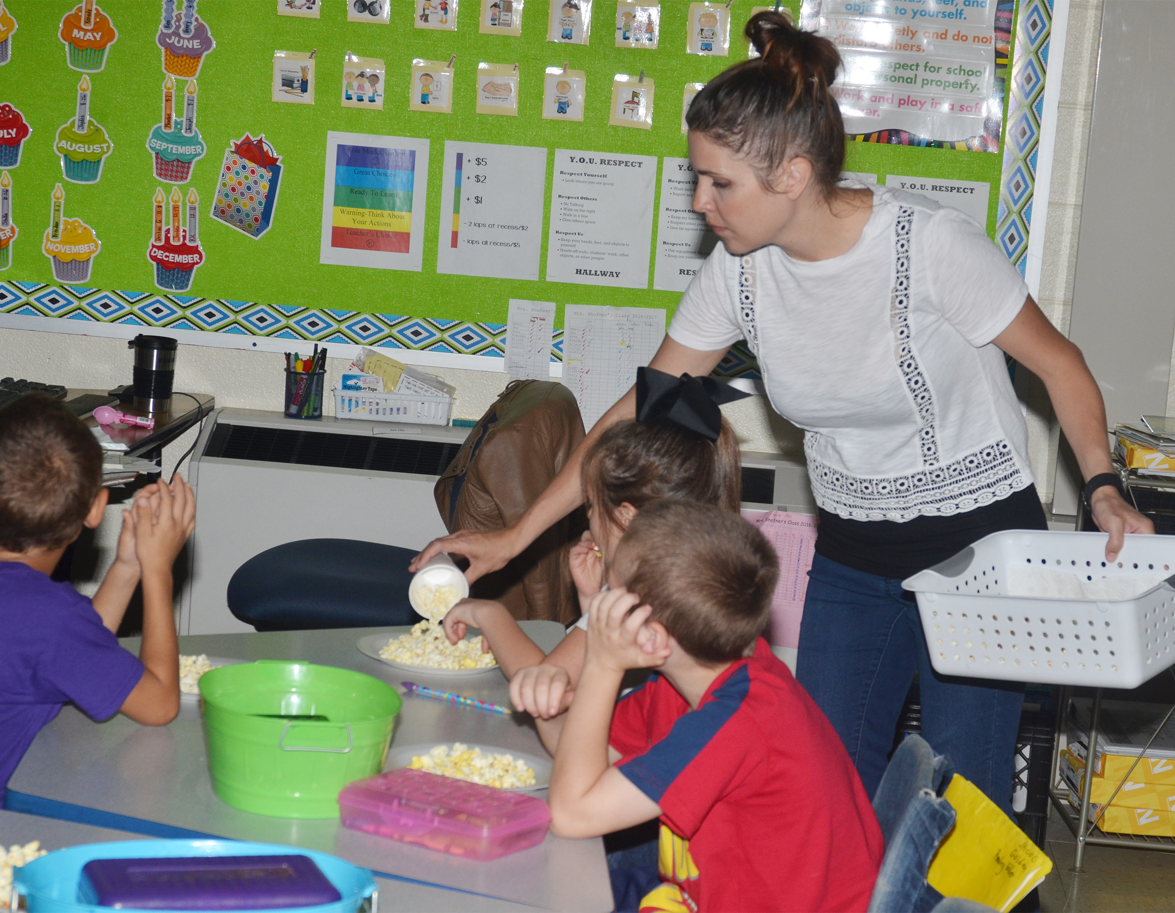 CES first-grade teacher Luci Shofner passes out popcorn to her students.