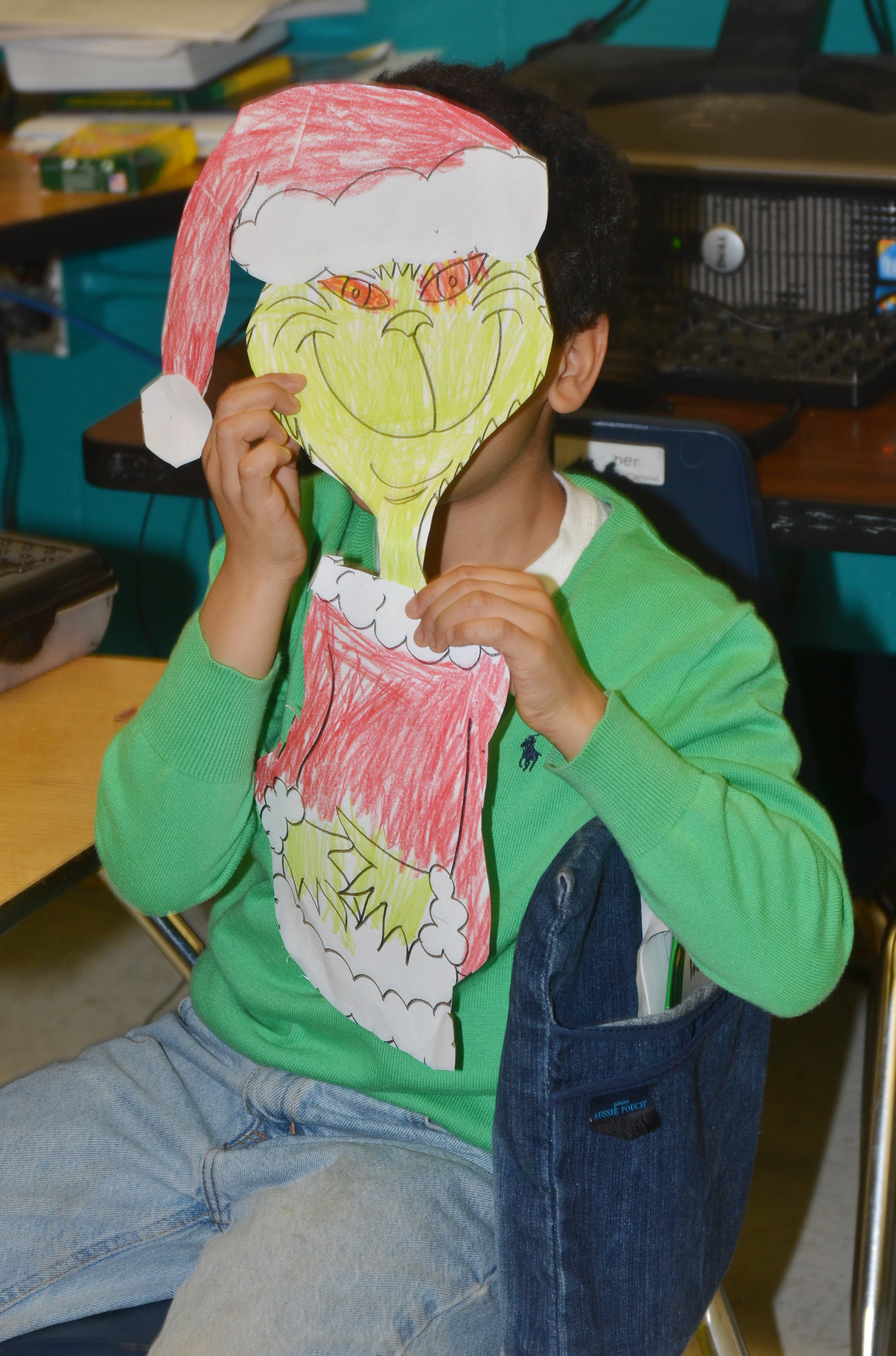 CES first-grader Ahryan Wilson smiles as he poses as the Grinch.