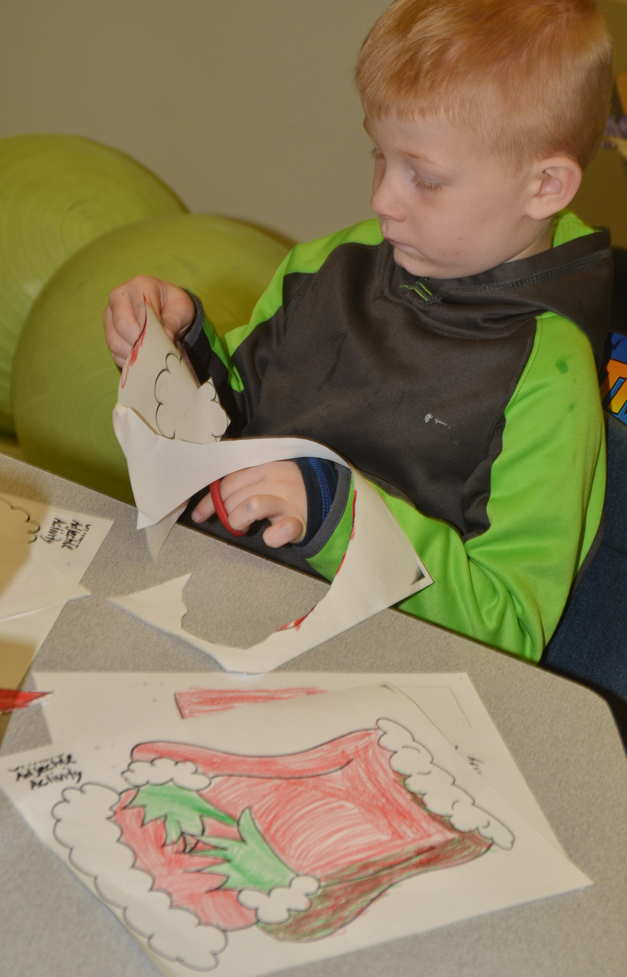 CES first-grader Jayden Maupin colors and cuts out the Grinch.