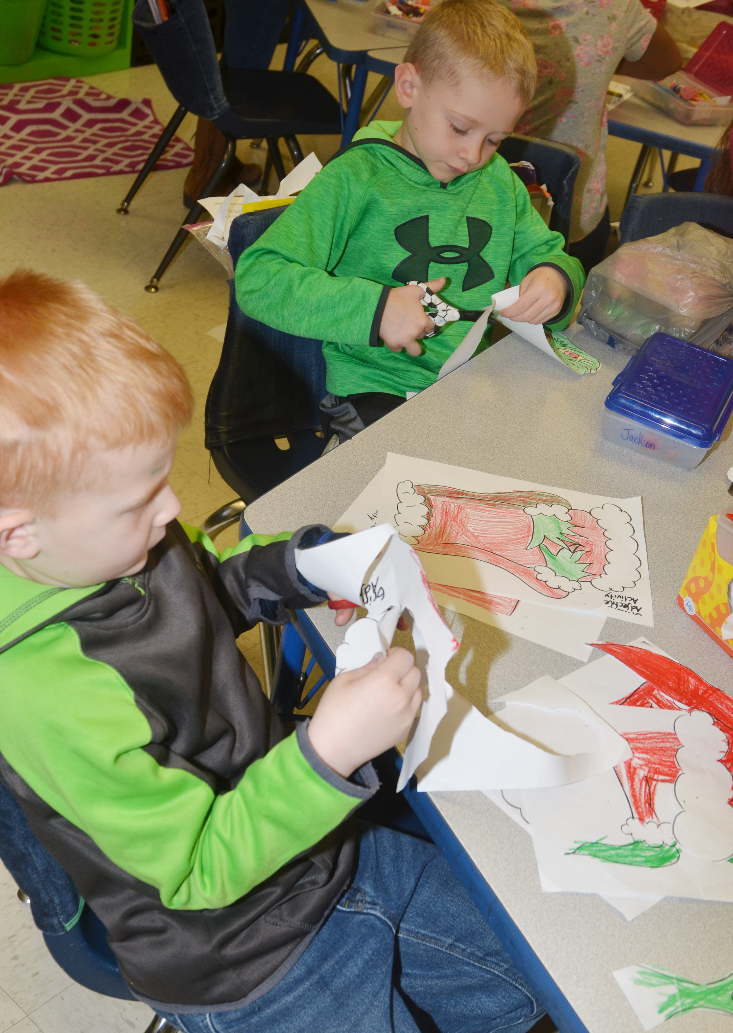 CES first-graders Jayden Maupin, at left, and Jackson Wright color the Grinch.
