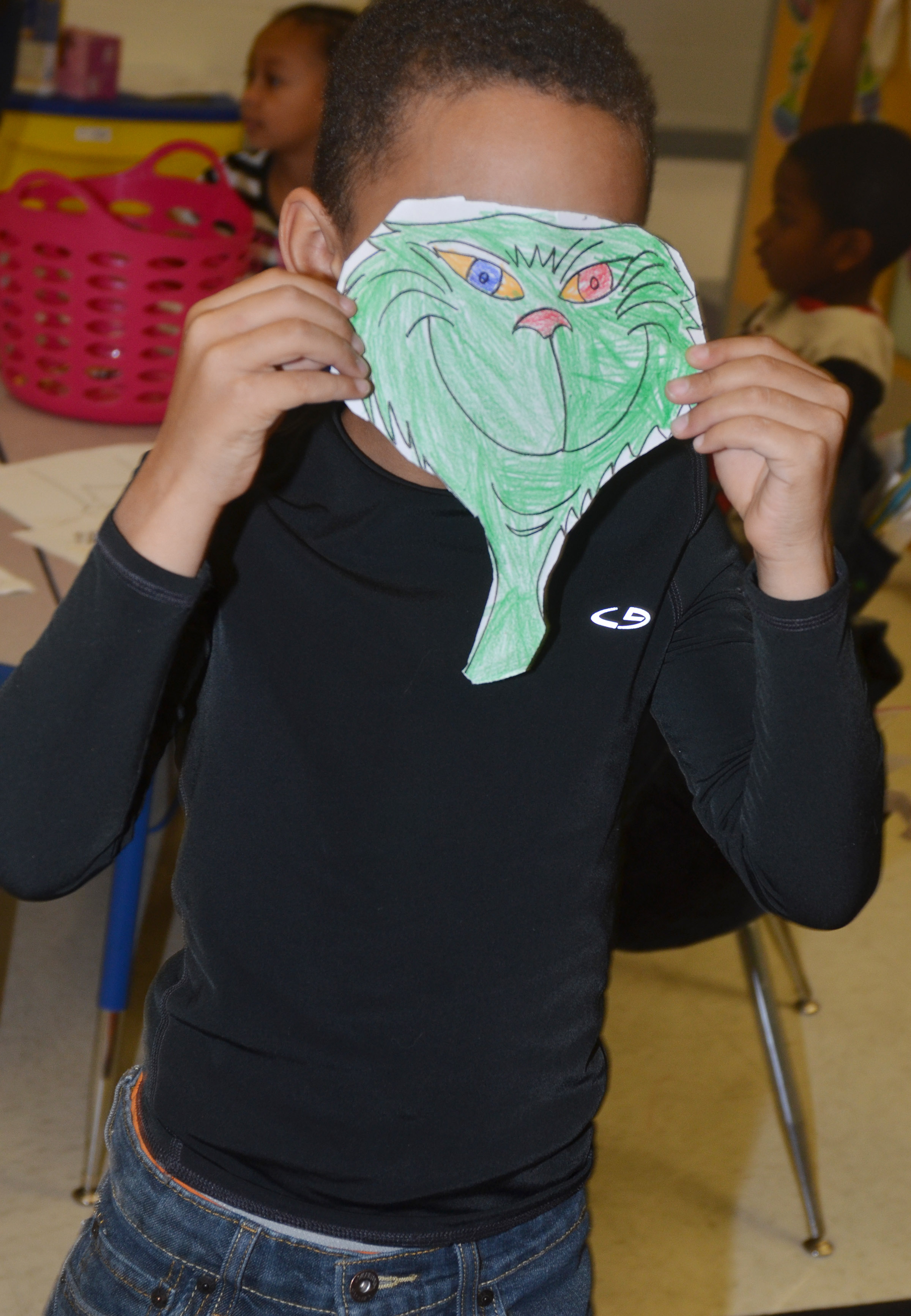 CES first-grader Quincy Travis smiles as he poses as the Grinch.