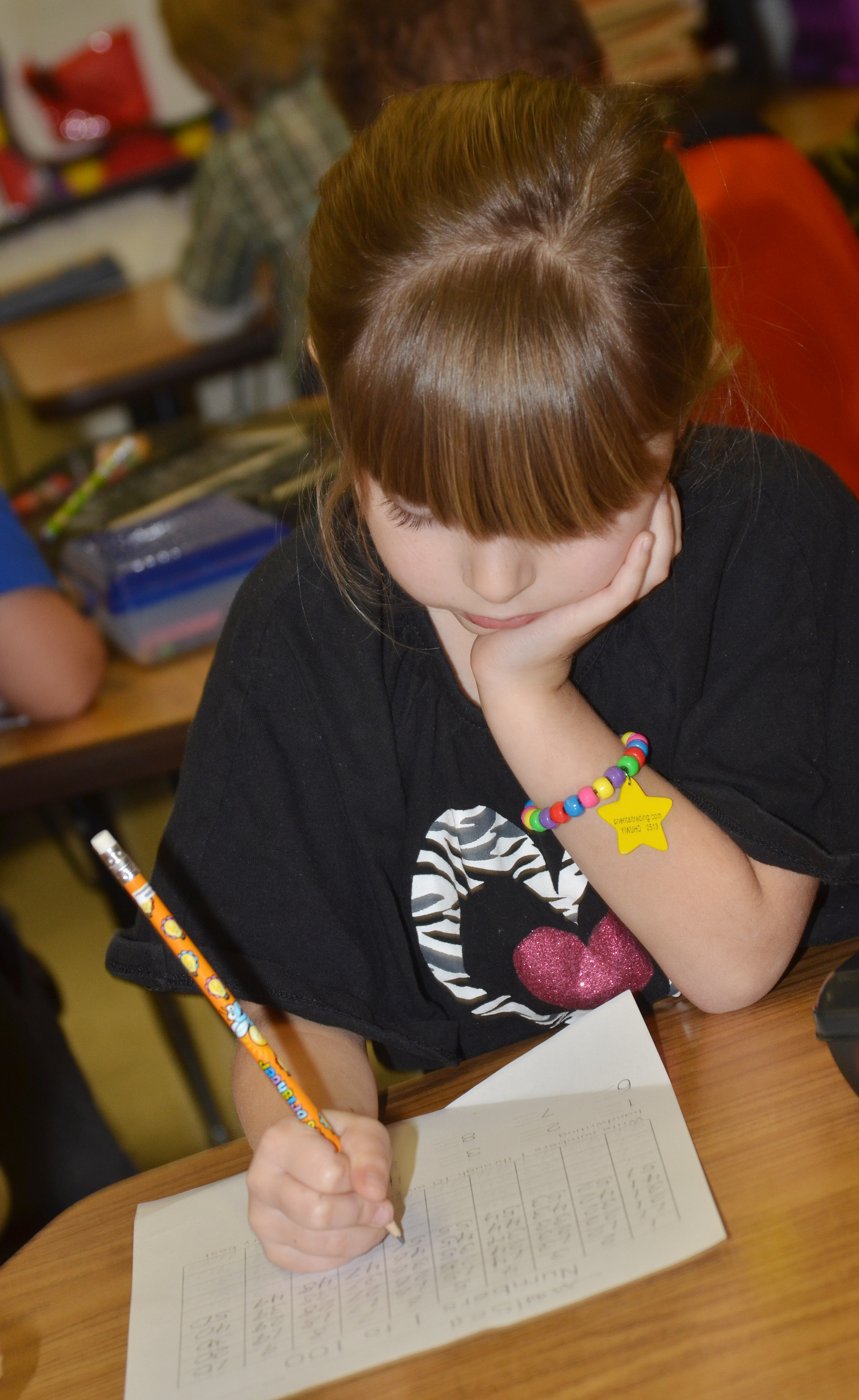 CES kindergartener Madison Wilhoite, wearing her 100 day bracelet, writes the numbers from 1 to 100.