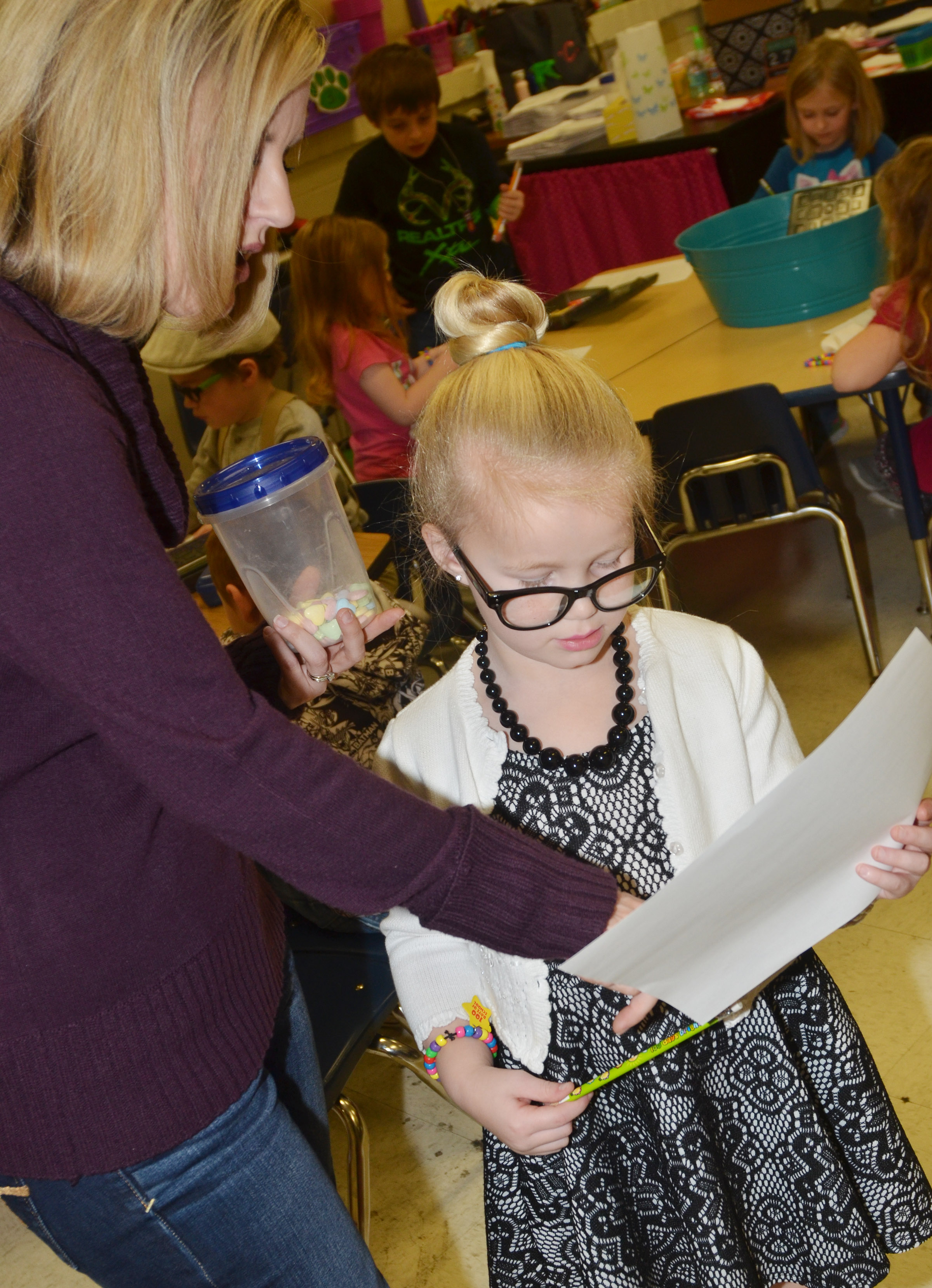 CES kindergartener teacher Leanna Cundiff helps Lillie Judd write the numbers from 1 to 100.