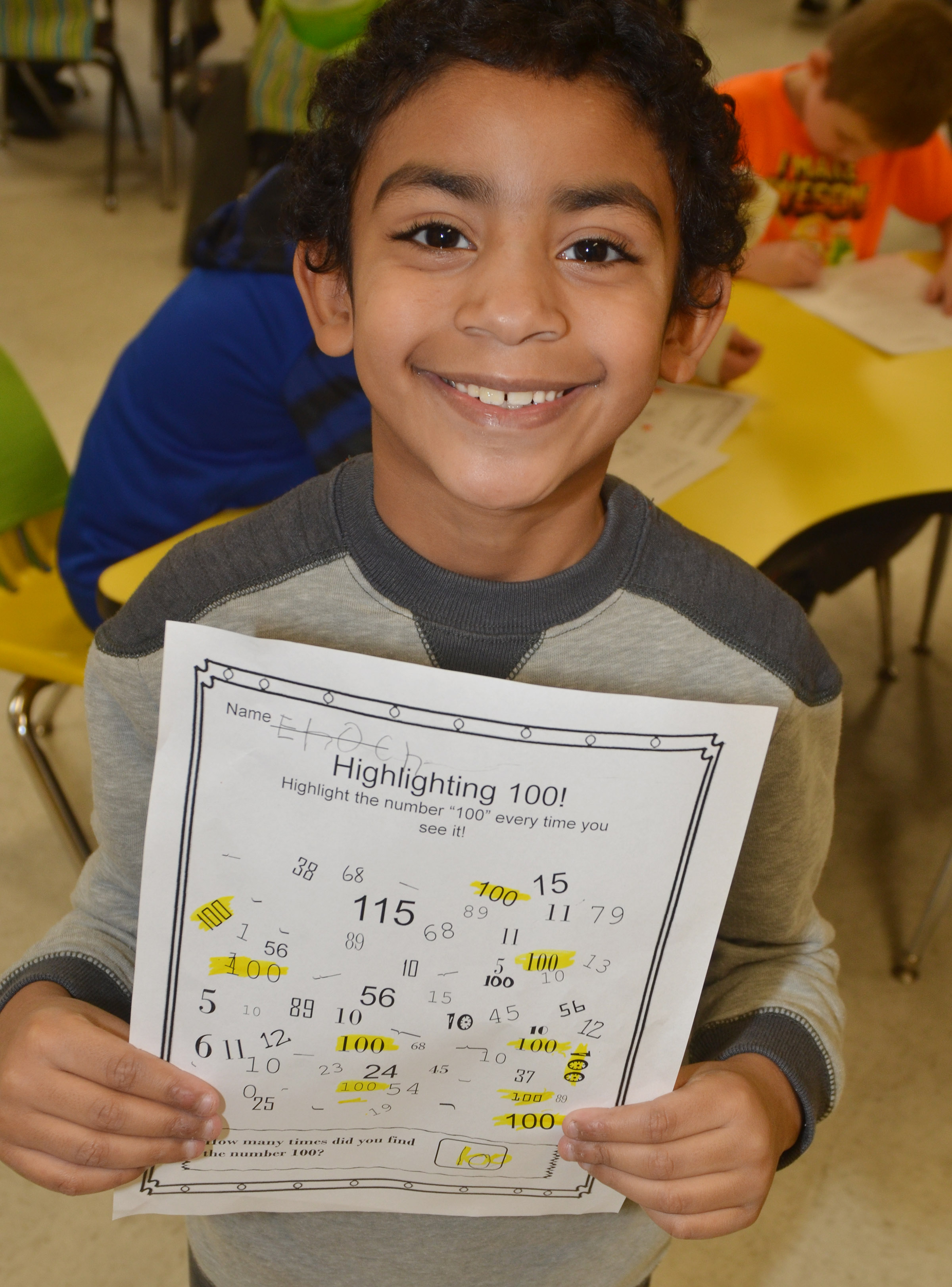 CES first-grader Enoch Smith highlights all the 100s in his worksheet of numbers.