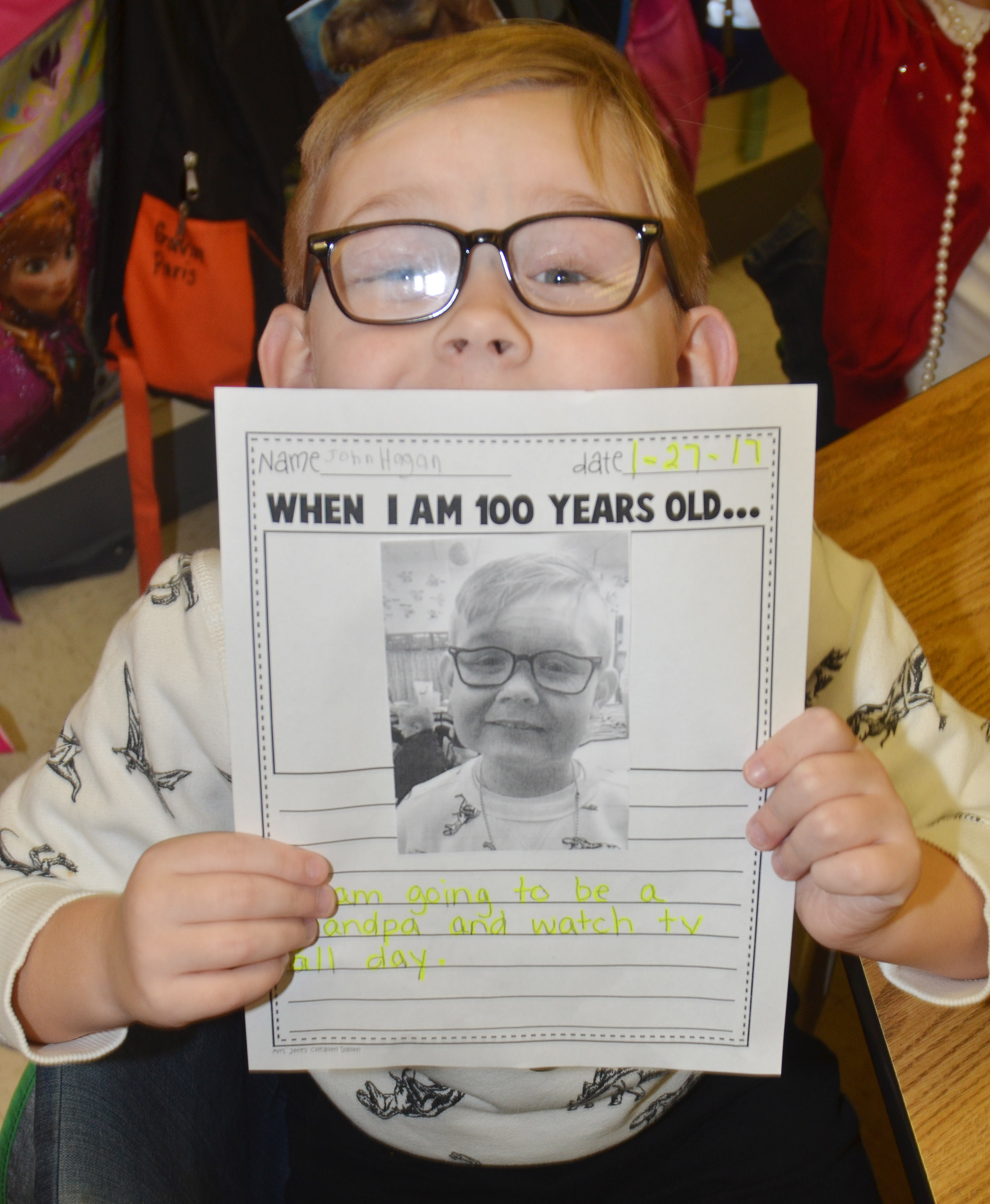 CES kindergartener John Hagan Newton holds a photo of what he will look like when he is 100 years old.