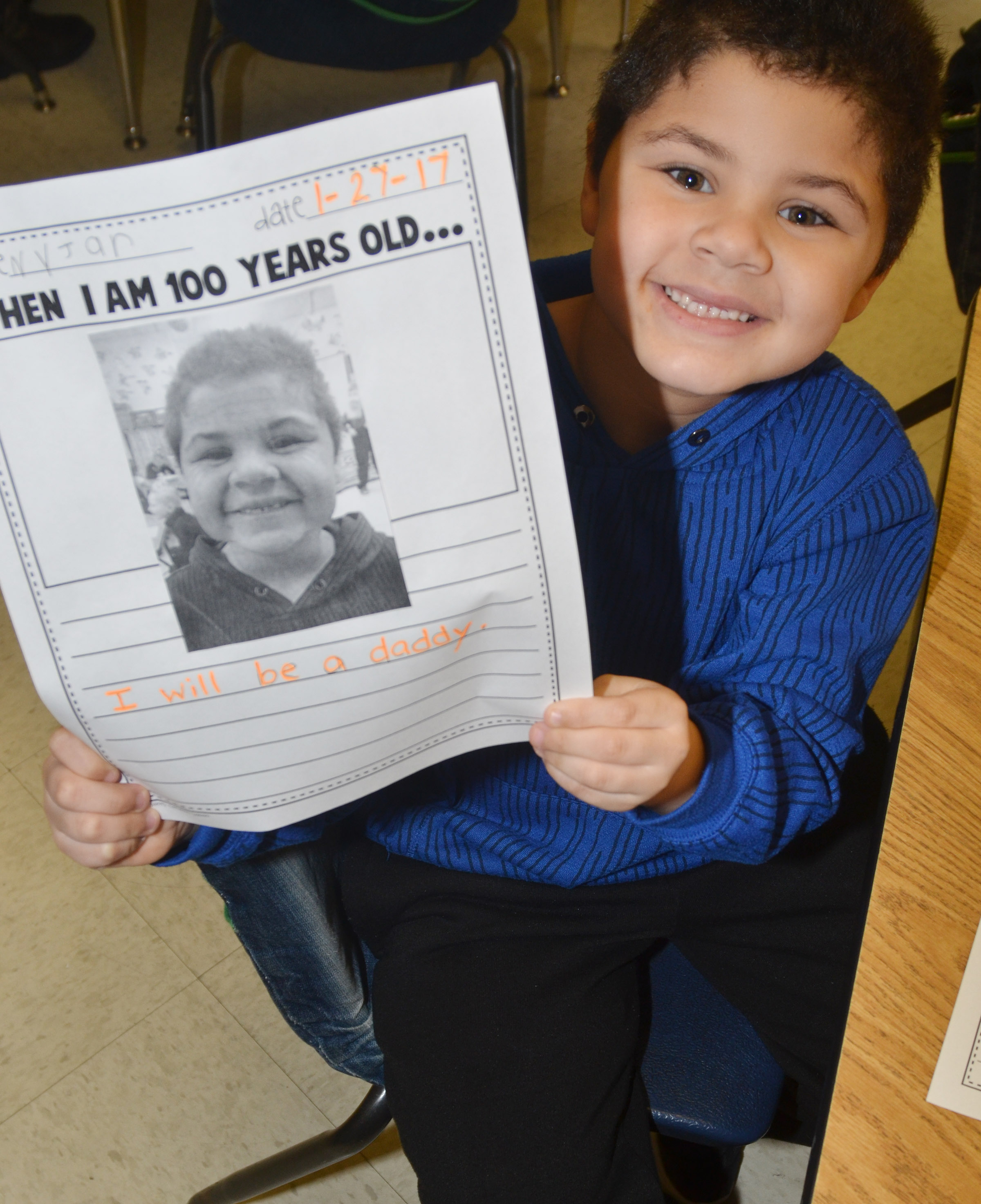 CES kindergartener NyJah Vaught holds a photo of what he will look like when he is 100 years old.