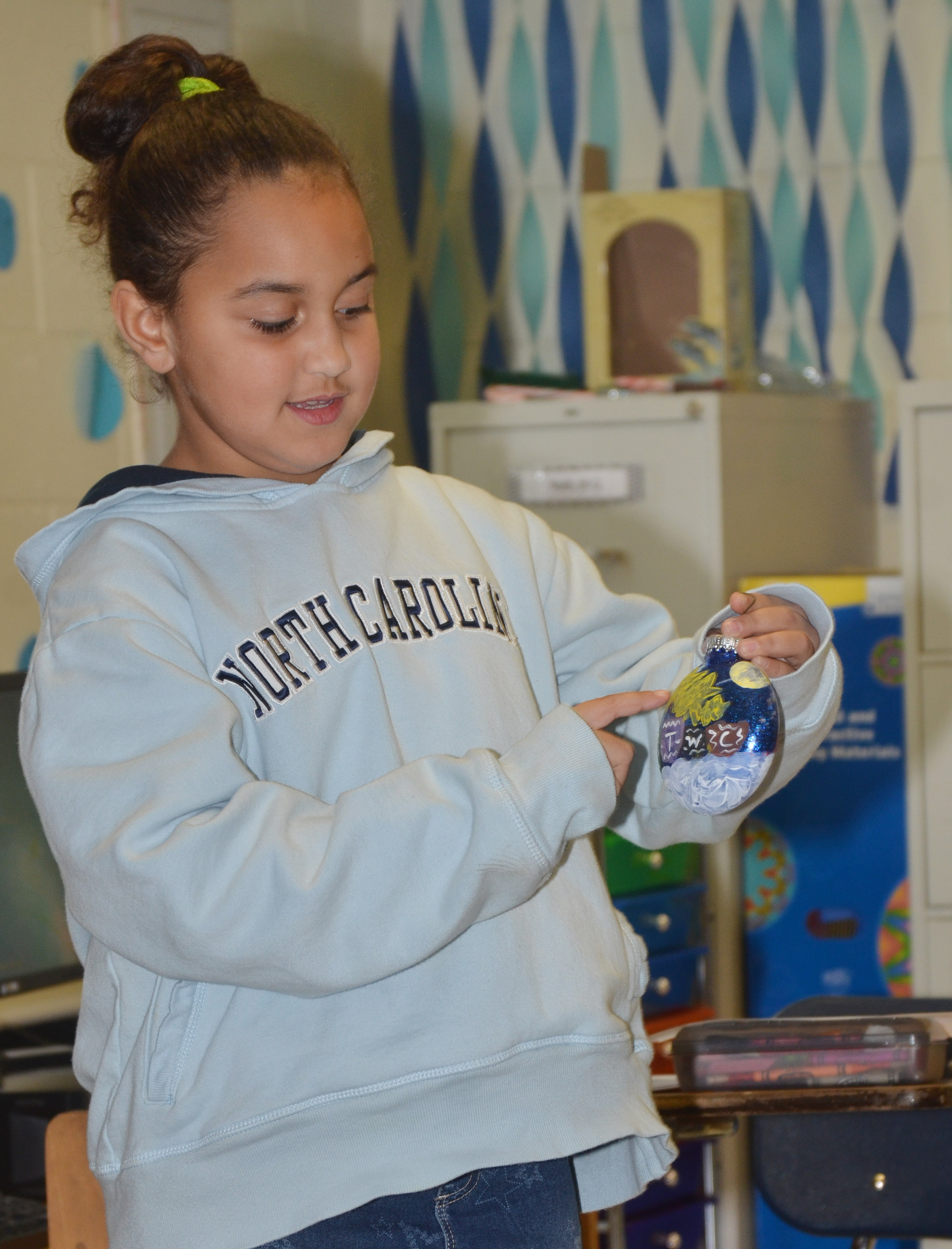 CES second-grader Maleigha Travis tells her classmates about her ornament.