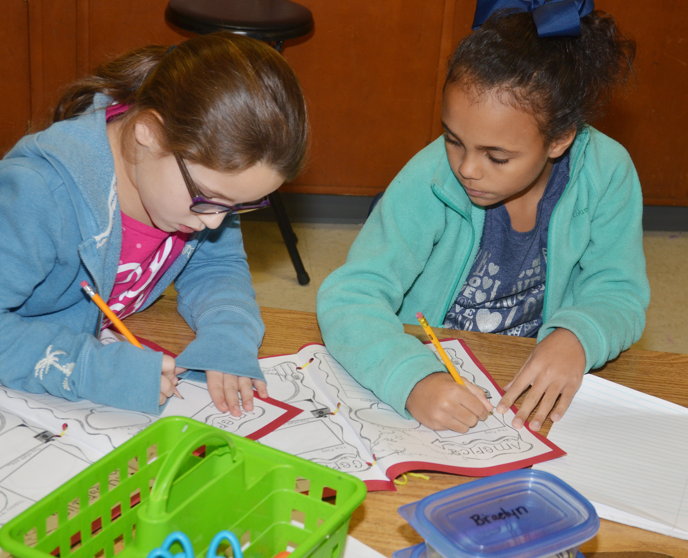 CES second-graders Keely Rakes, at left, and Braelyn Taylor draw in their Christmas tradition books.