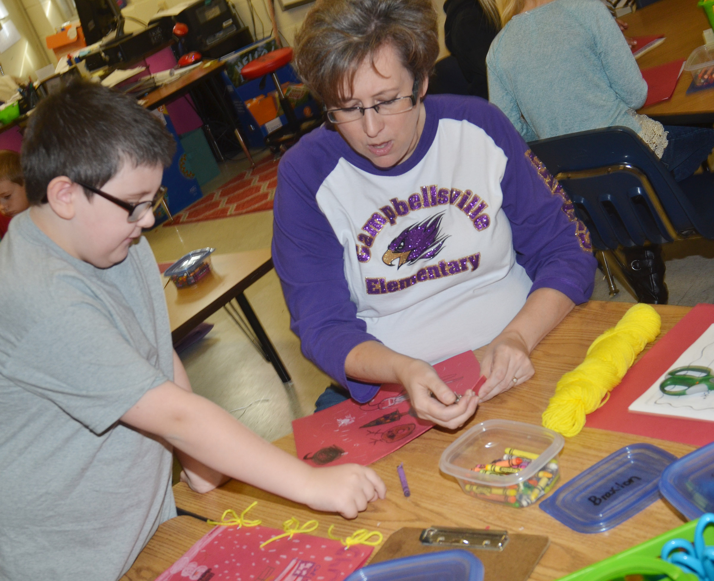 CES second-grade teacher Lynne Horn helps Mason Jackson tie his book together.