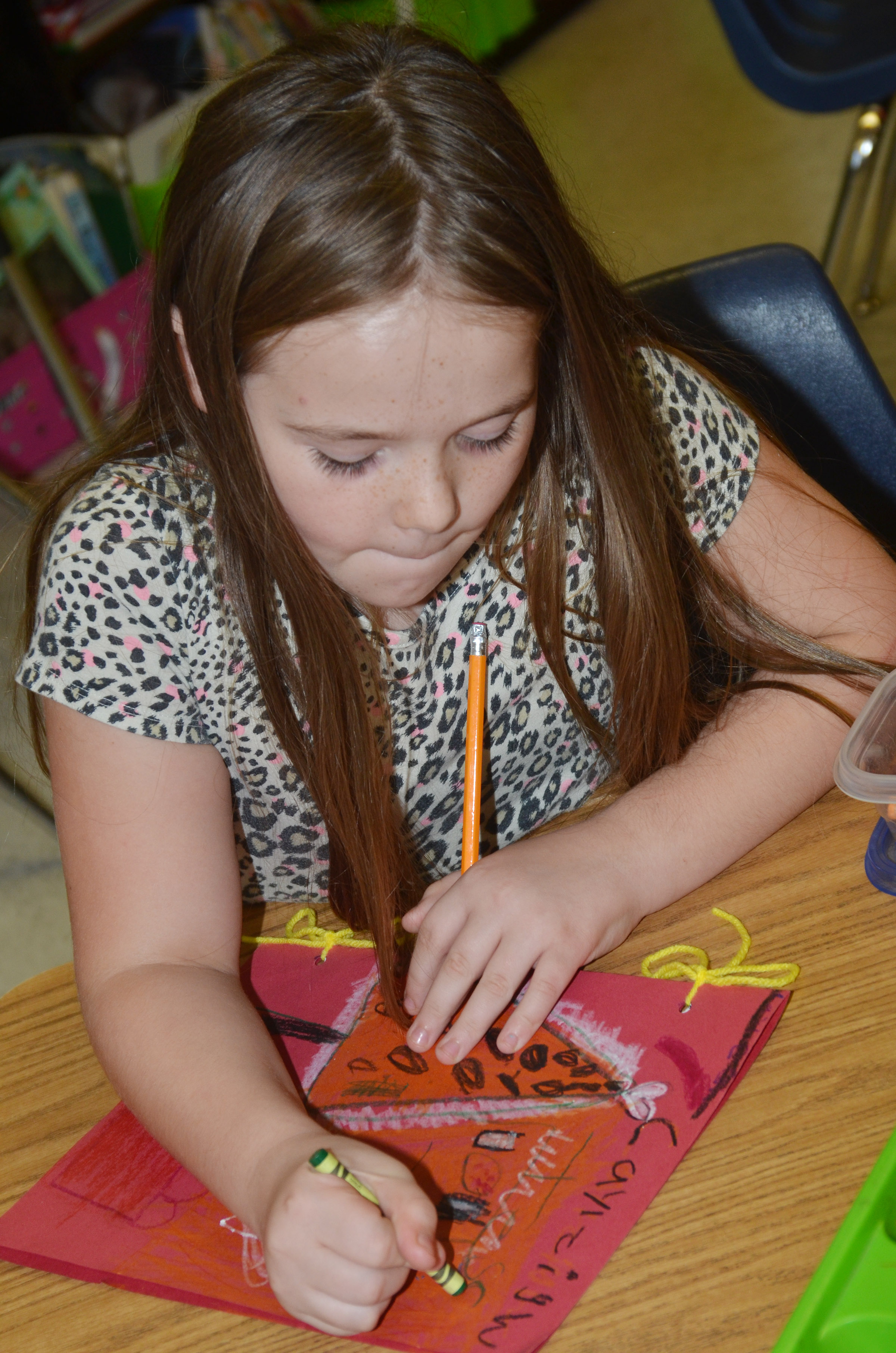 CES second-grader Cayleigh Underwood colors the cover of her Christmas tradition book.
