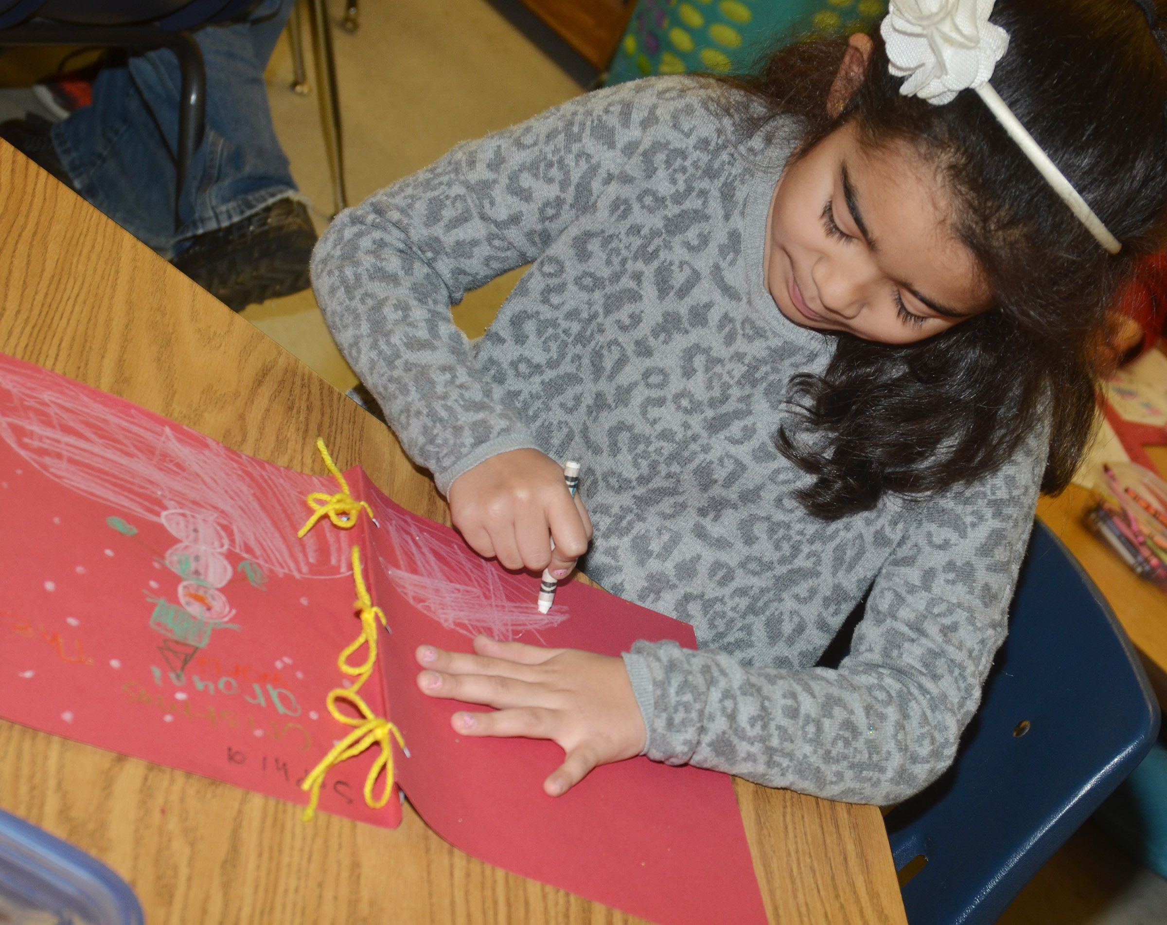 CES second-grader Sophia Santos colors the cover of her Christmas tradition book.