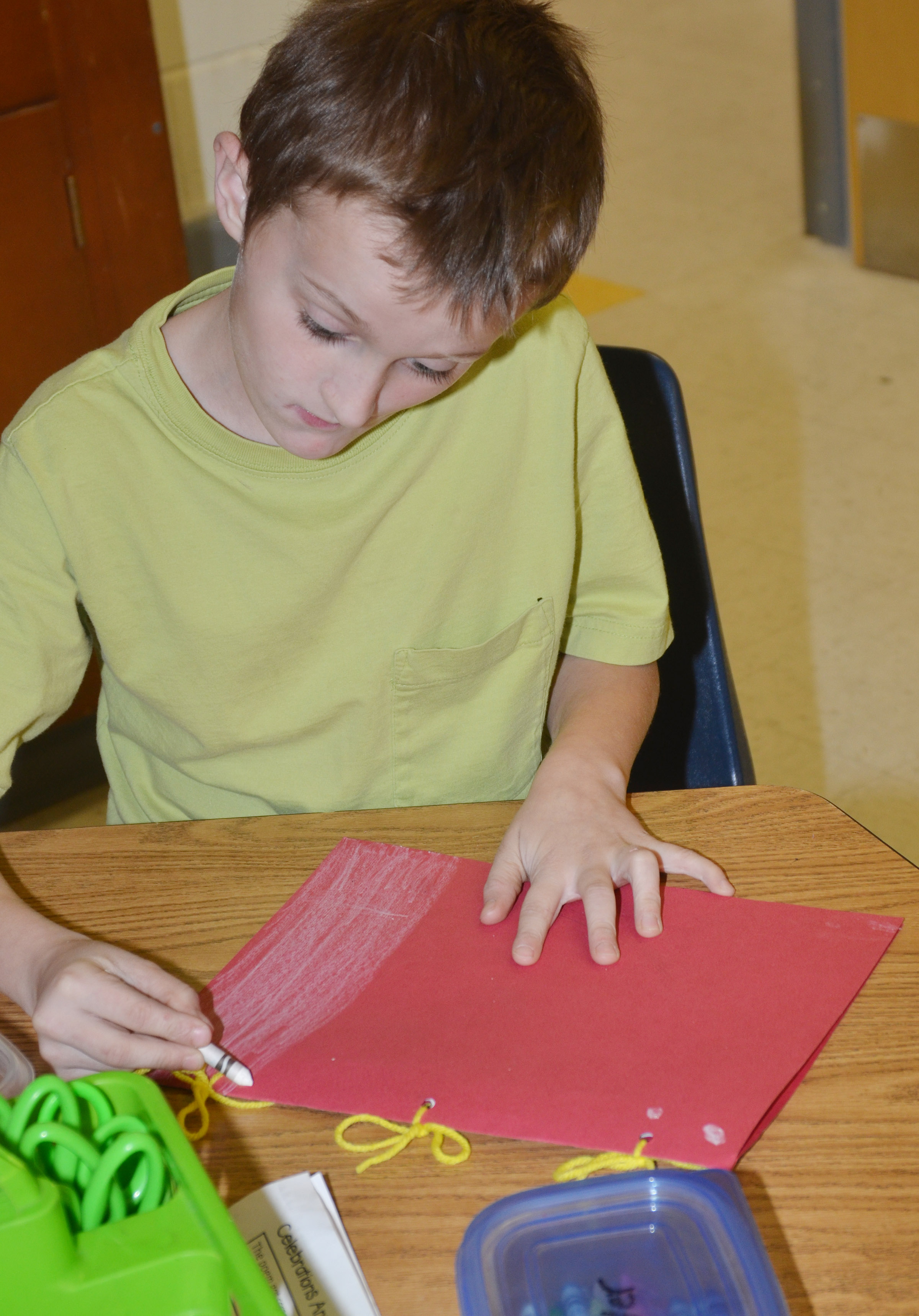 CES second-grader Zachary Cox colors the back of his Christmas tradition book.