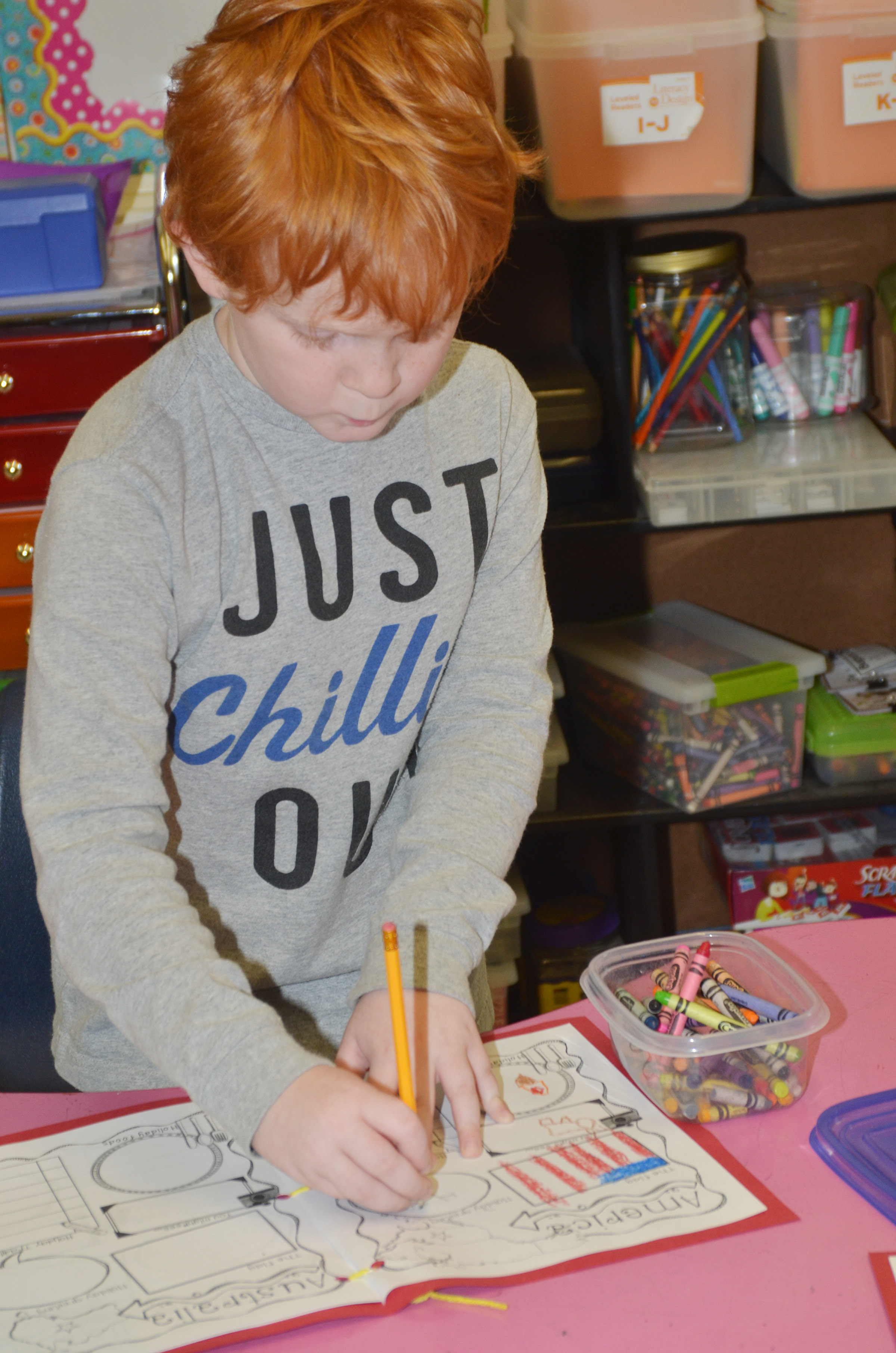 CES second-grader Gavin Martin draws in his Christmas tradition book.