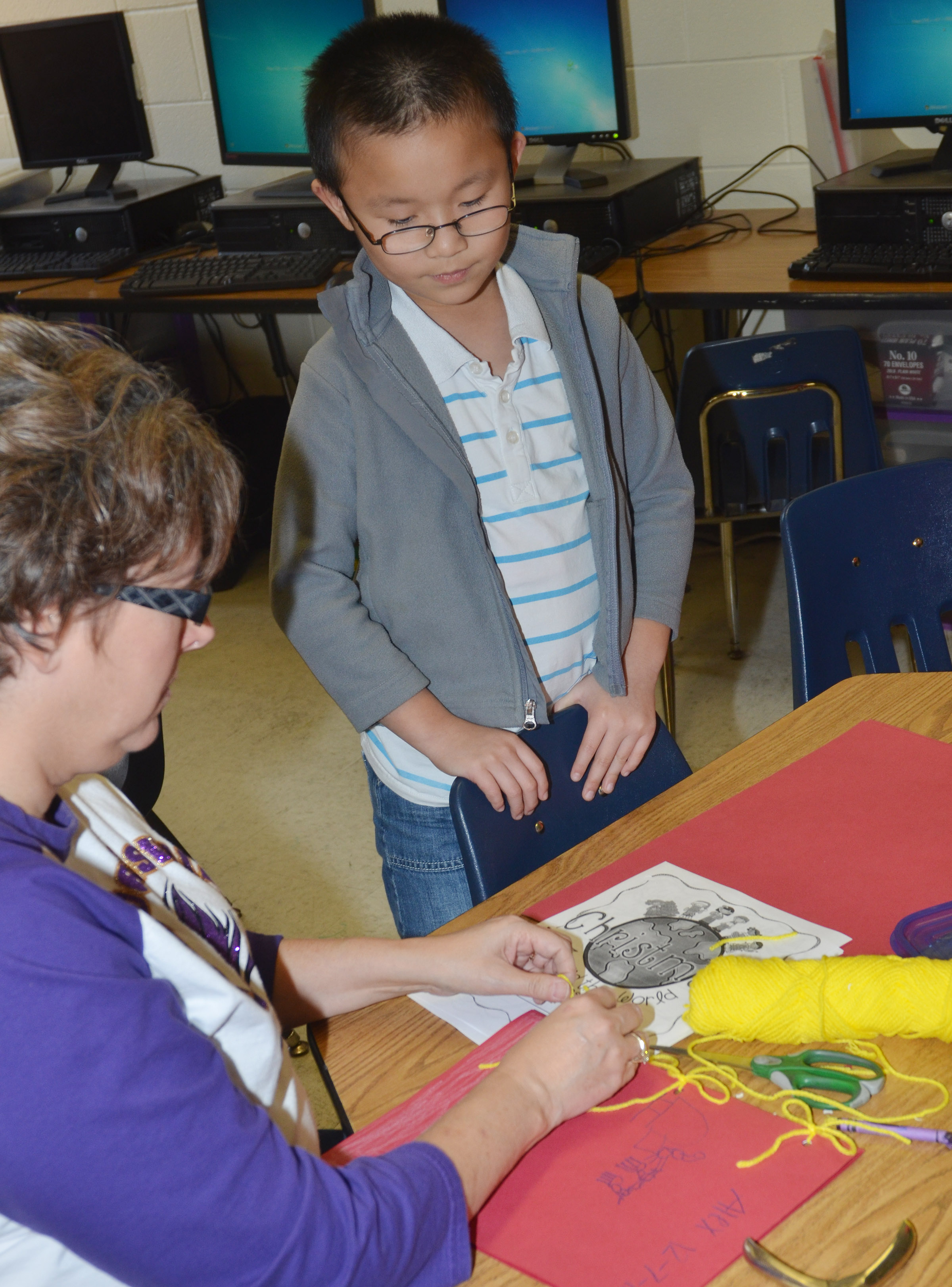 CES second-grade teacher Lynne Horn helps Alex Yang put his book together.