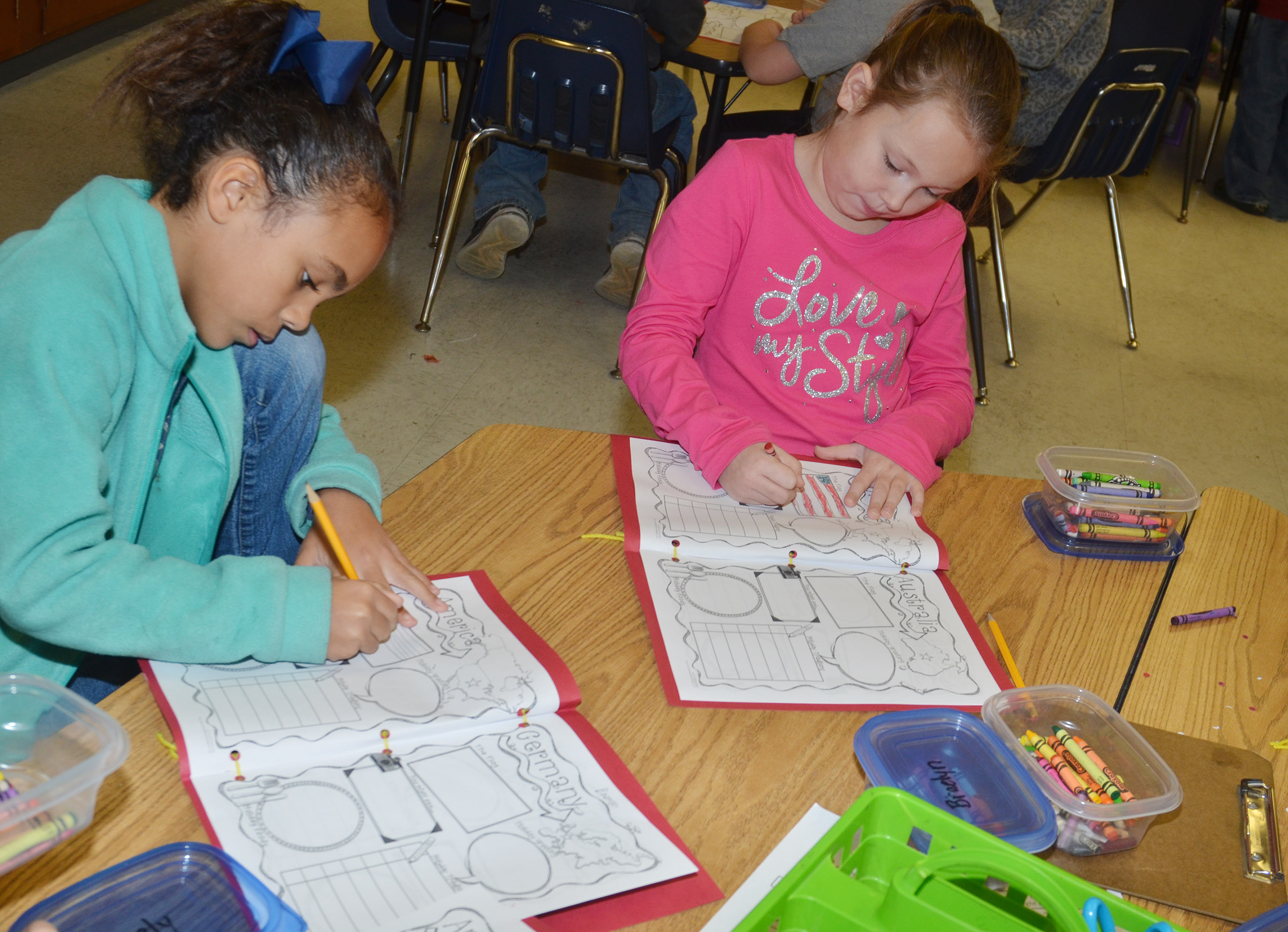 CES second-graders Braelyn Taylor, at left, and River McFarland draw in their Christmas tradition books.