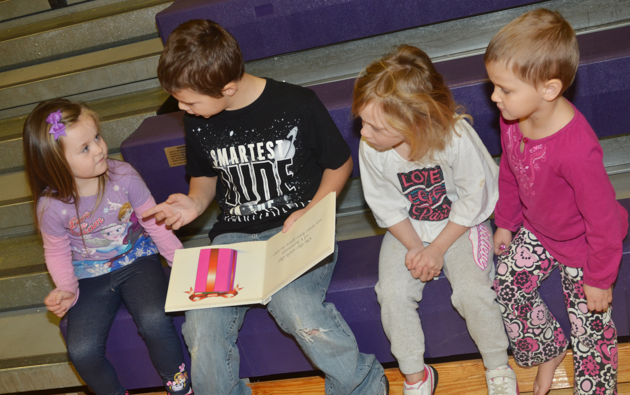 CES second-grader Jaxson Hunt reads to preschool students, from left, Tori Clark, Aubree Hall and Adaia Taylor.