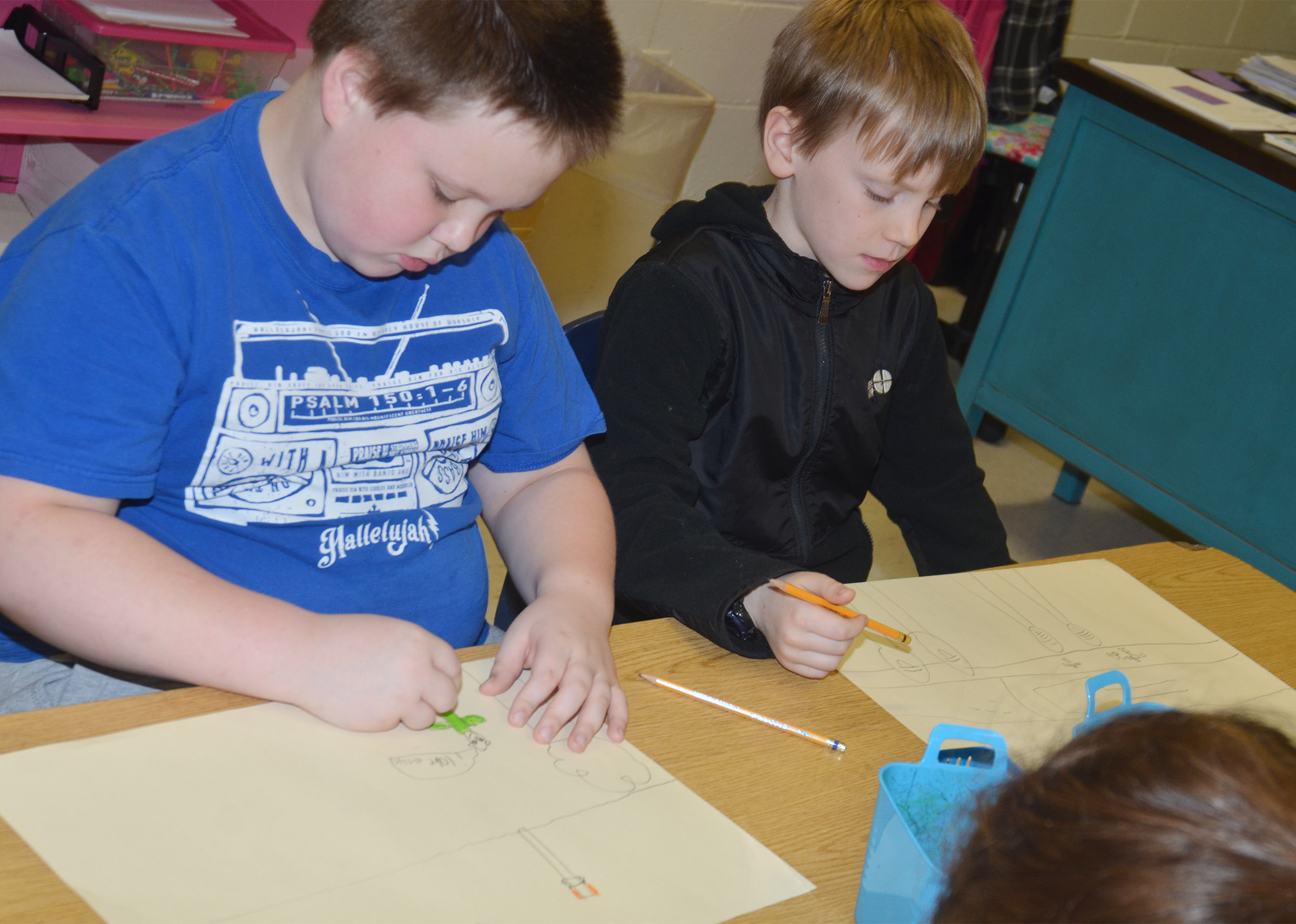 CES third-graders Jace Cox, at left, and Connor Coots draw their murals of what they enjoy doing in Campbellsville.