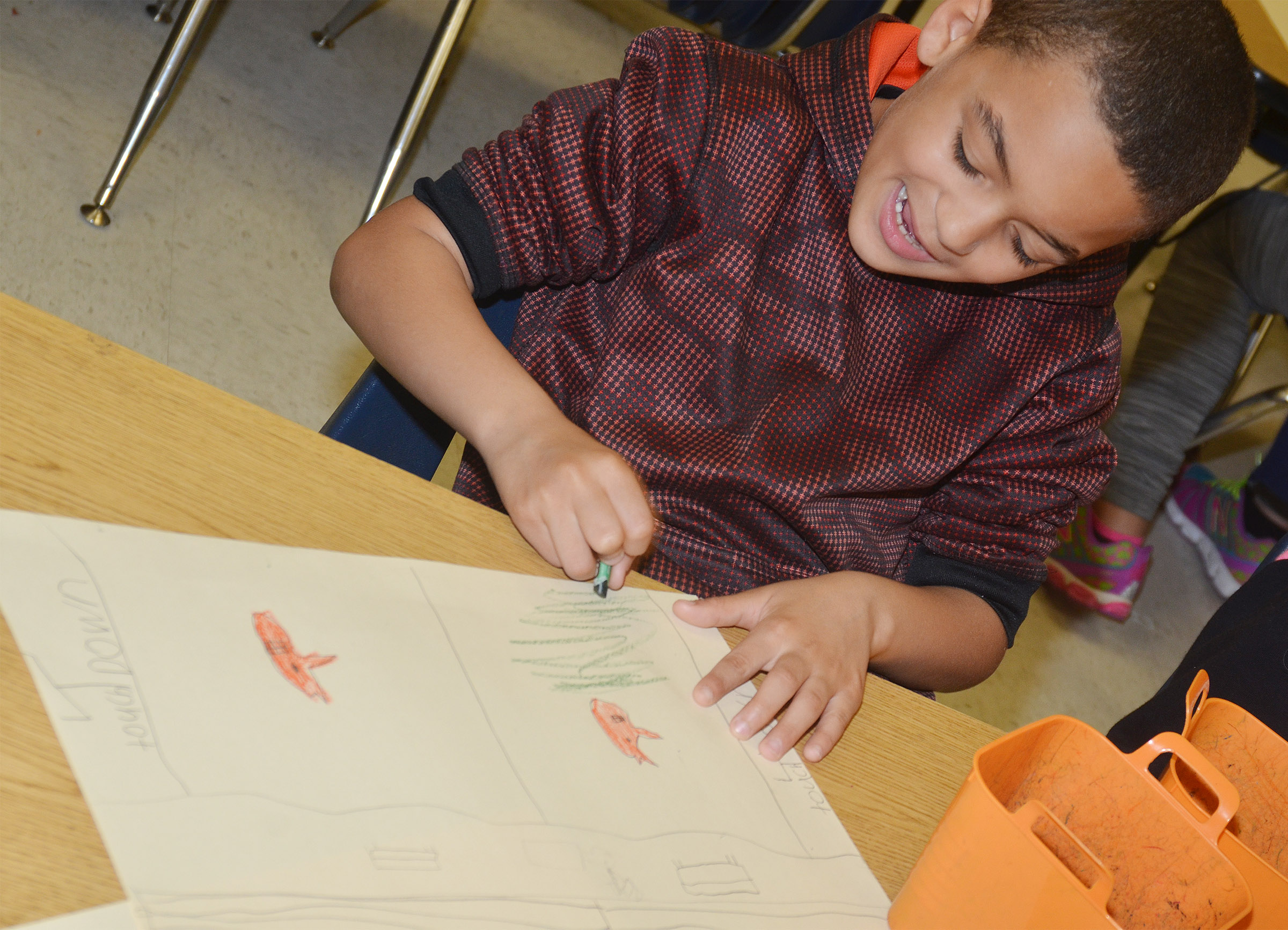 CES third-grader Jaden Barbee draws his mural of what he enjoys doing in Campbellsville.