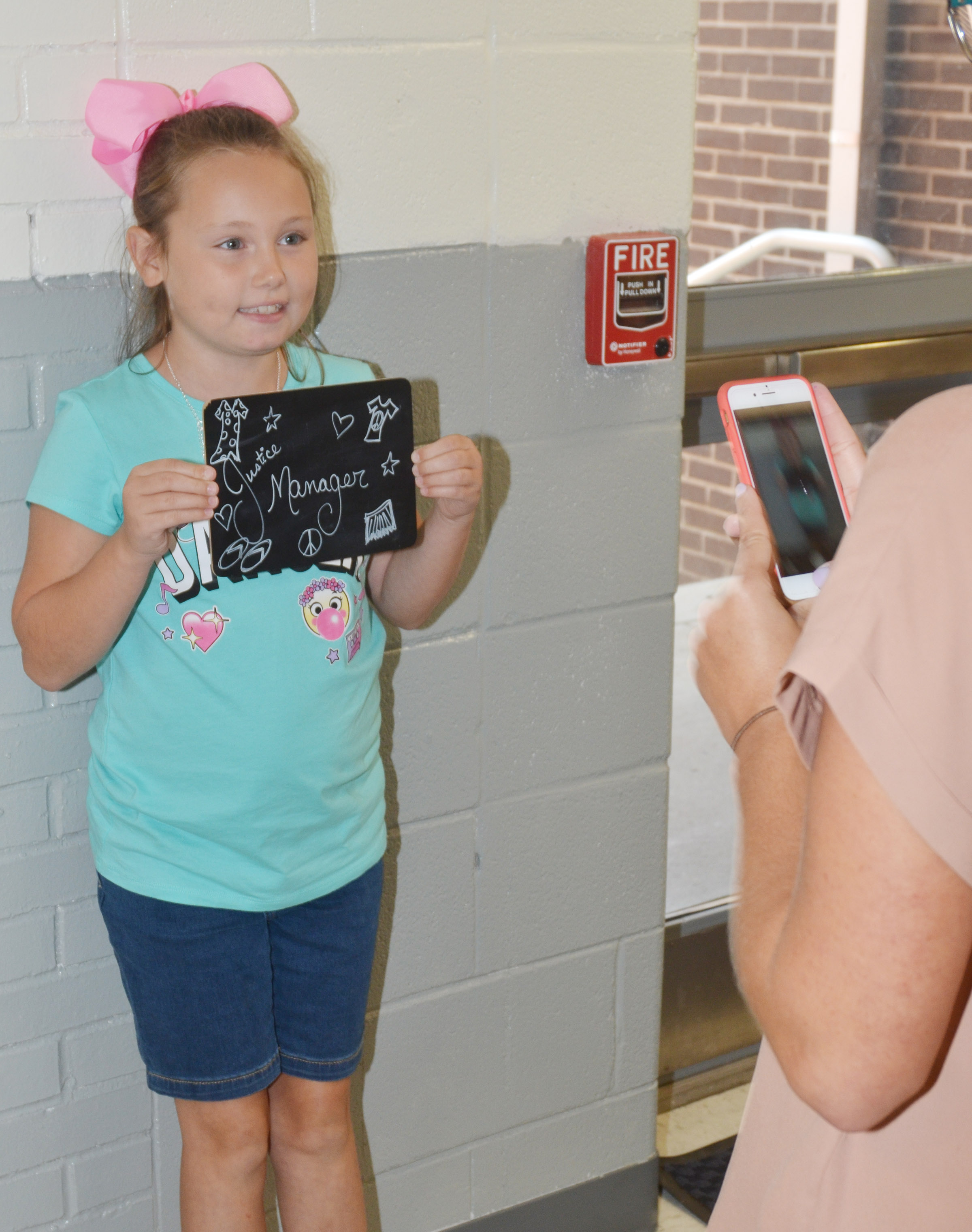 CES third-grader River McFarland, who wants to be a manager at Justice when she gets older, smiles for a photo.