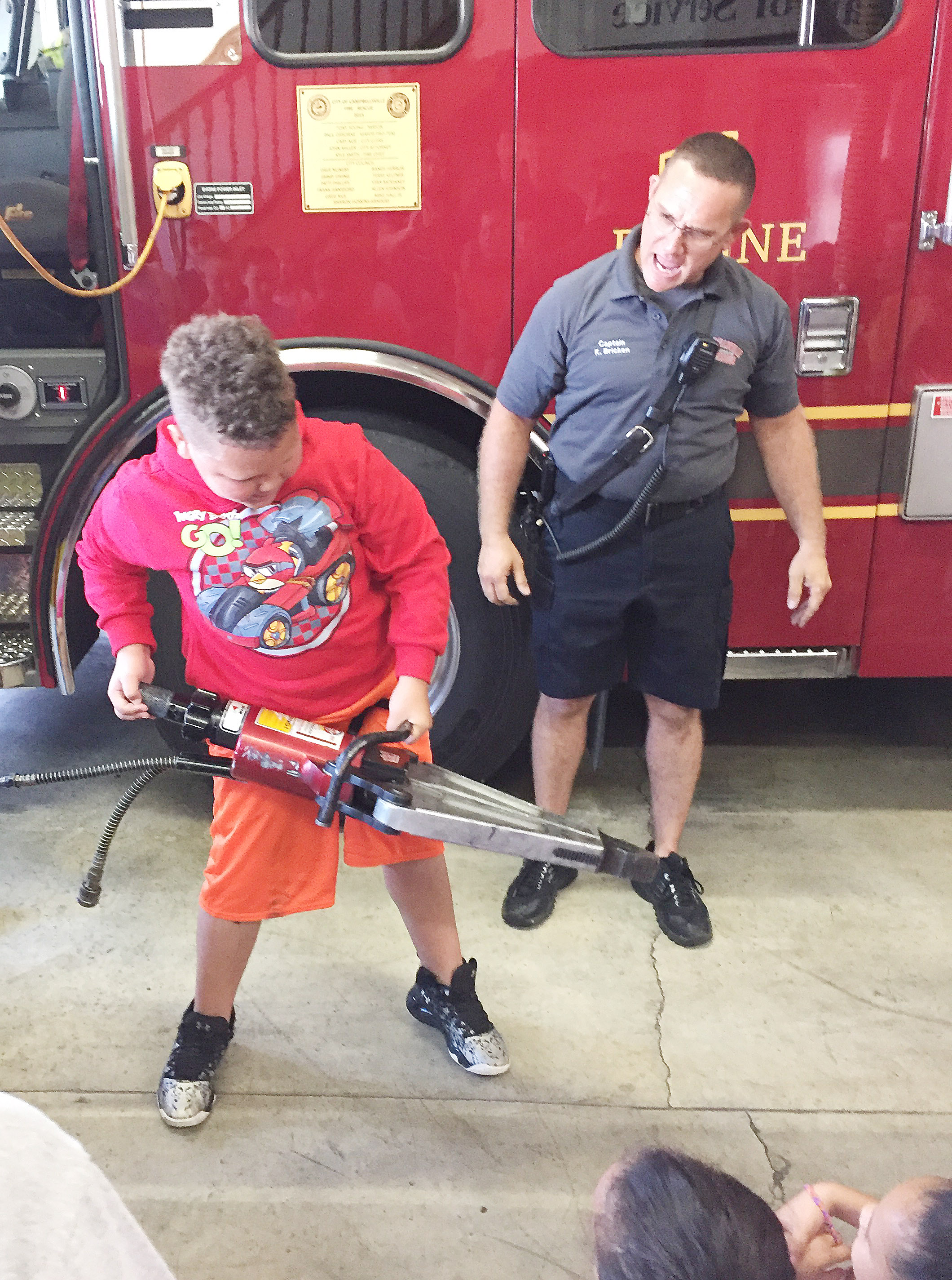 CES third-grader Drevonte Gurley picks up the Jaws of Life as Campbellsville Fire & Rescue Captain Keith Bricken talks to CES third-graders about how he and his fellow firefighters use the equipment.