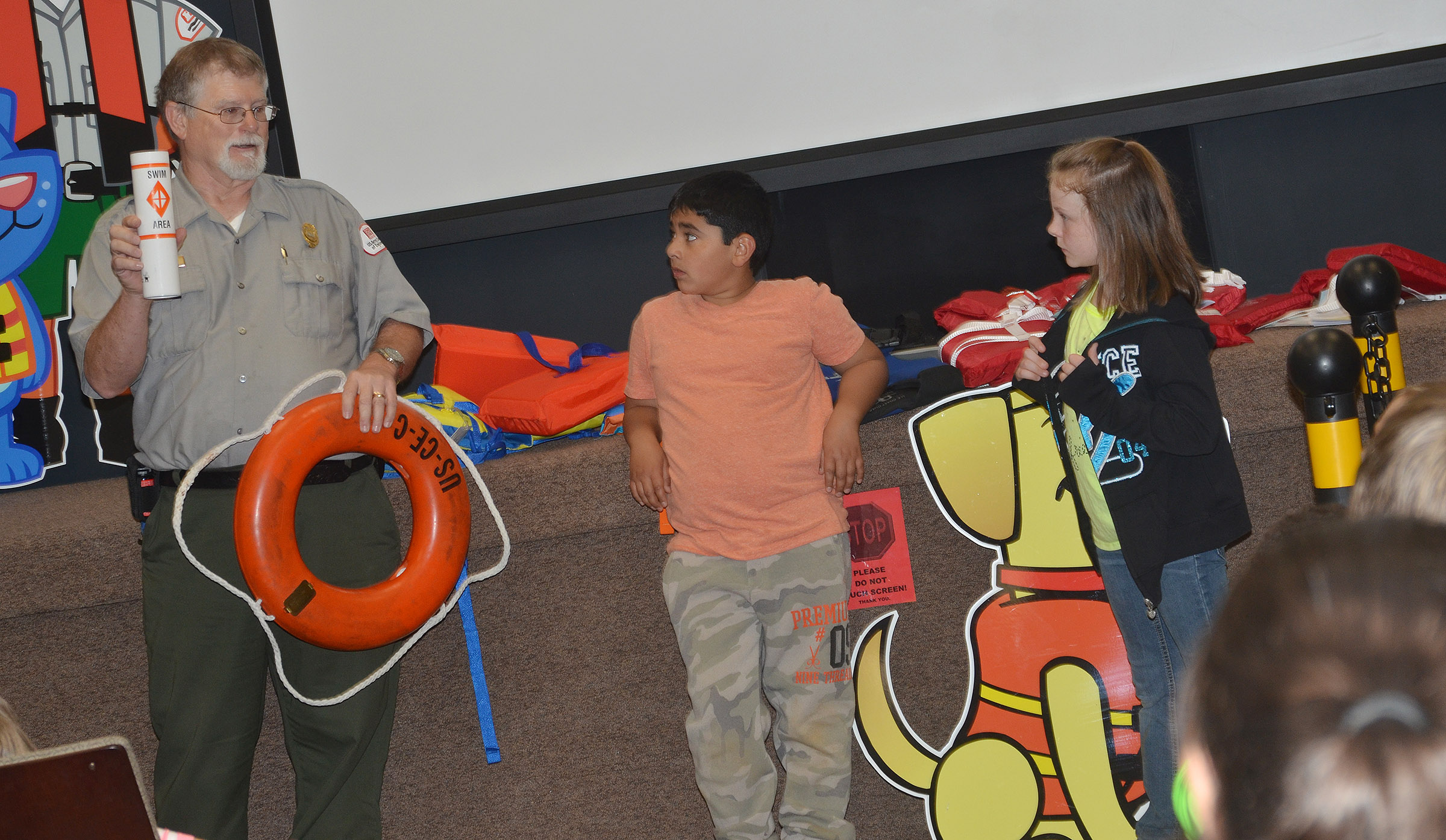 Park Ranger David Goode talks to CES third-graders about other equipment that can keep people safe in the water. Cody Tamez, center, and Jaylen Clark volunteered to try on life jackets to see how they are supposed to fit.