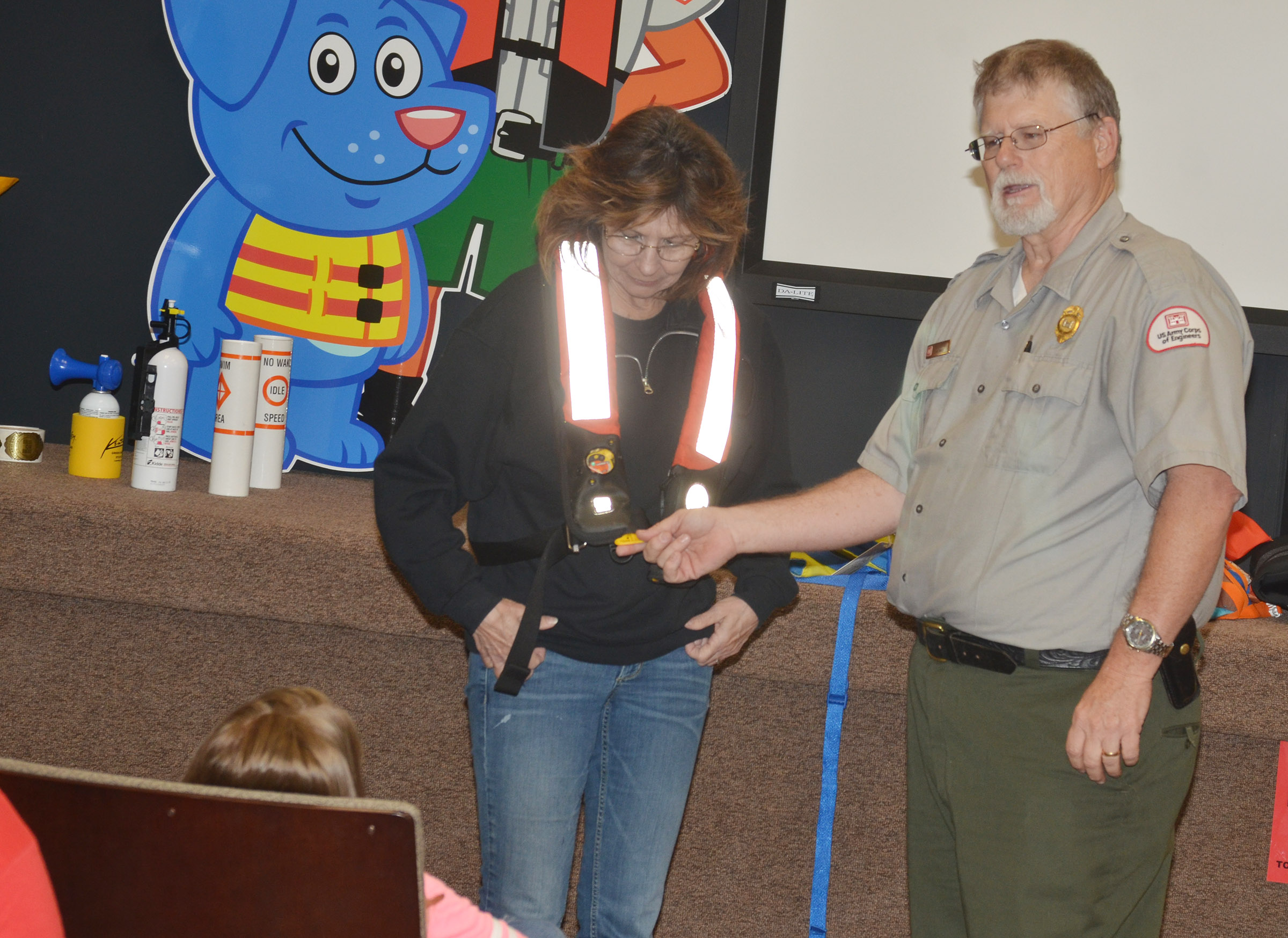 Park Ranger David Goode helps CES third-grade teacher Marcia Sharp try on a life jacket.