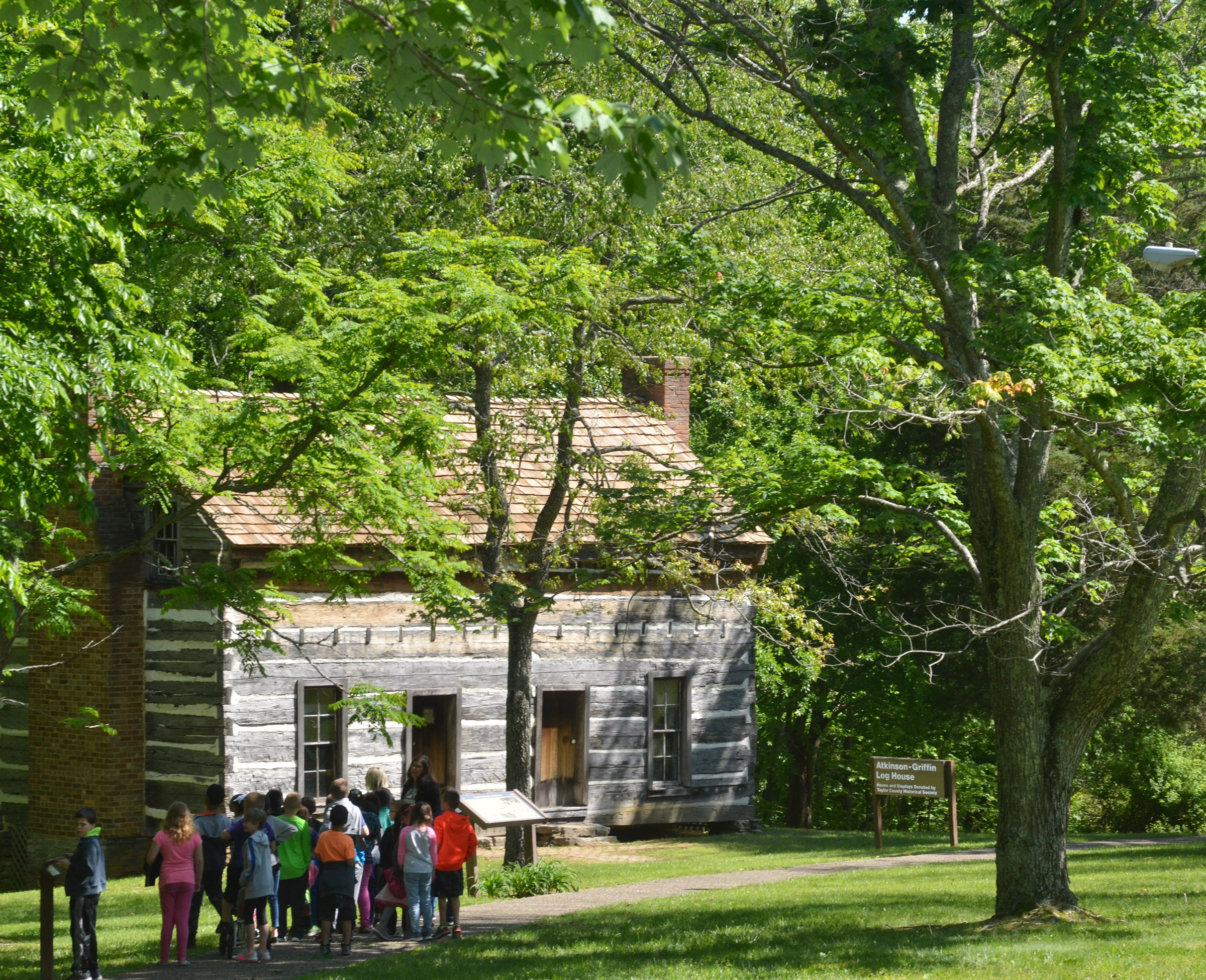 CES third-graders walk to the Atkinson-Griffin Log House for a tour.